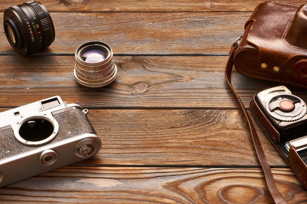 Vintage cameras and lenses on wooden background