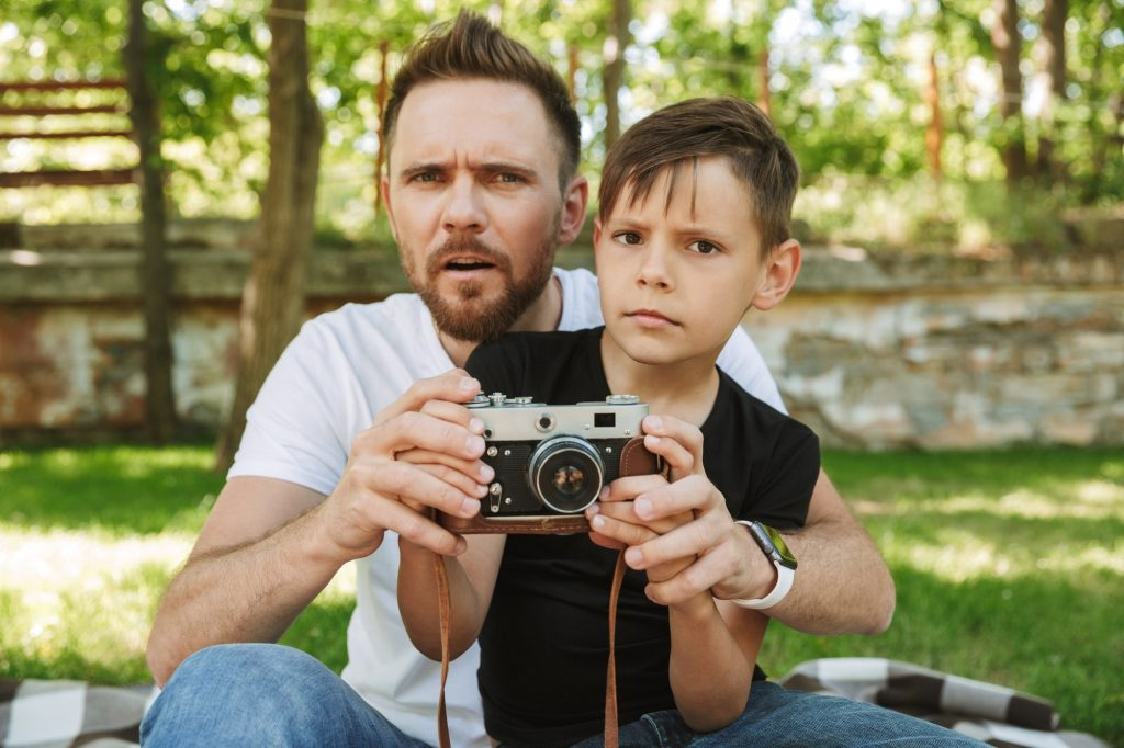 Young confused father sitting with his little son photographing.