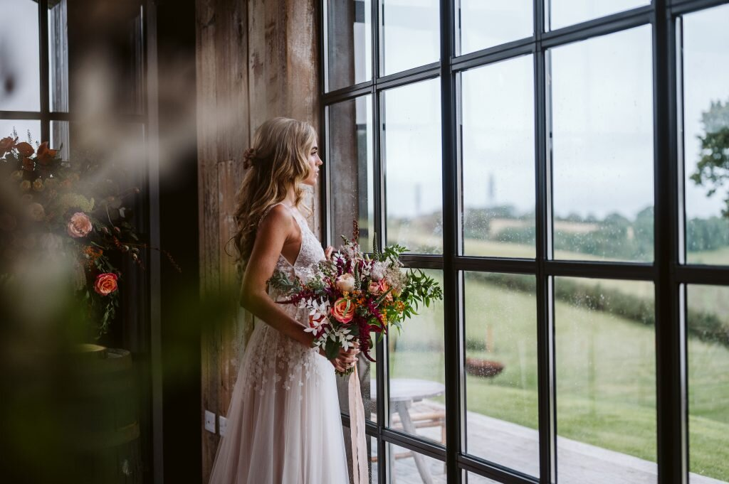 Bride in wedding dress looking out barn window