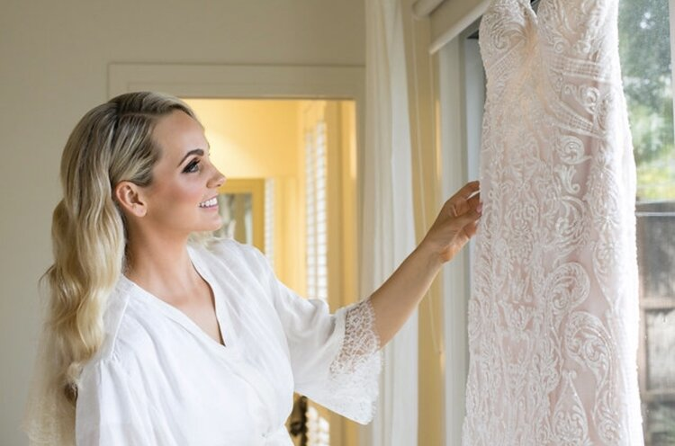 Bride smiling and gazing at dress in living room window