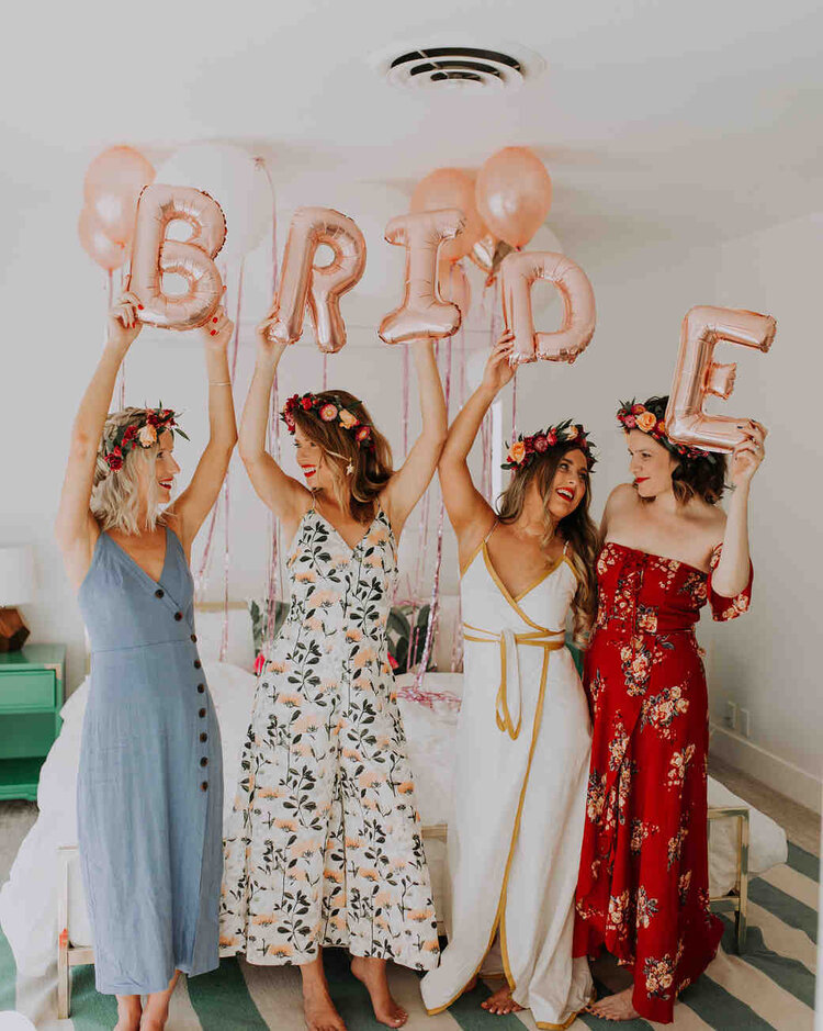 Bridesmaids holding up sign at home