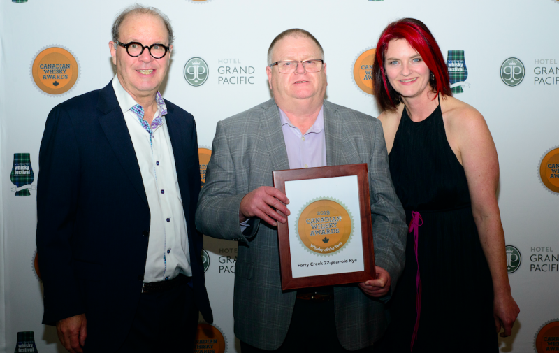 Photo caption: Forty Creek distiller, Bill Ashburn (centre) accepts the award for Whisky of the Year from head judge and awards founder, Davin de Kergommeaux (l), and co-host Heather Leary (r).  Photo Credit: Jen Steele  From the 2019 Whisky Awards