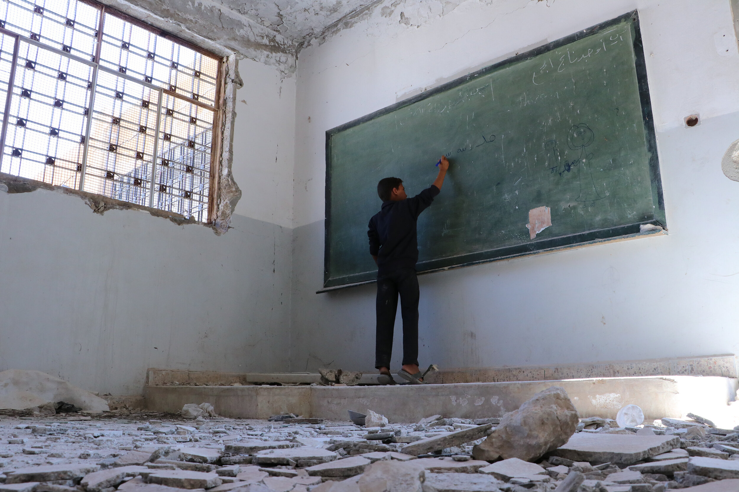 A boy writes on the board of a damaged classroom in Idlib governorate, Syria in July 2019. © 2019 Save the Children's partner in Syria, Hurras Network.