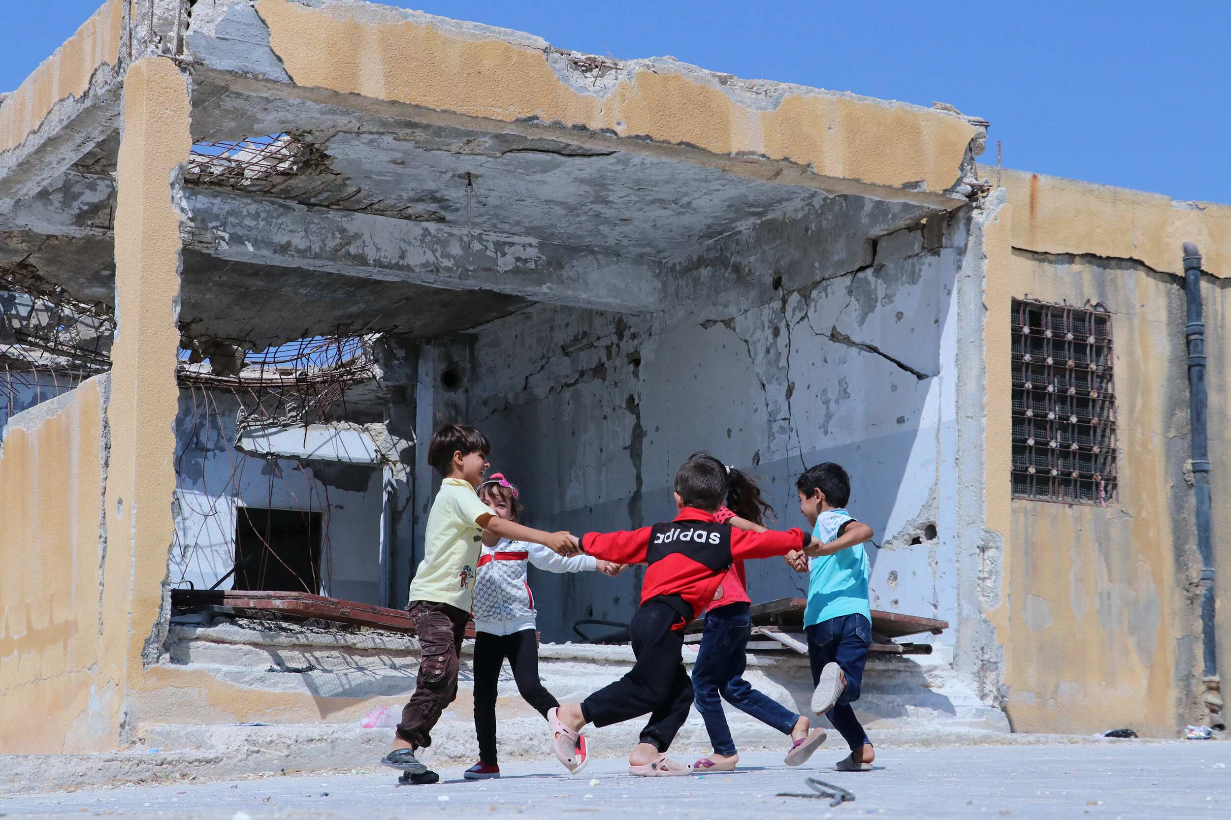 Children play outside their war-damaged school near Idlib, Syria. © 2019 Save the Children