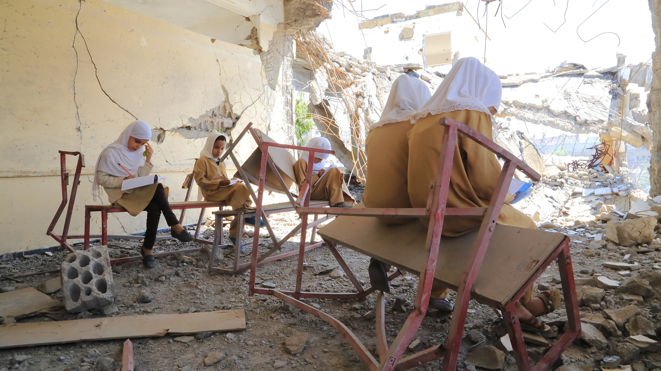 Girls study in a classroom destroyed by airstrikes in Taizz, Yemen. © 2019 UNICEF/UN1275387/Al-Sabri