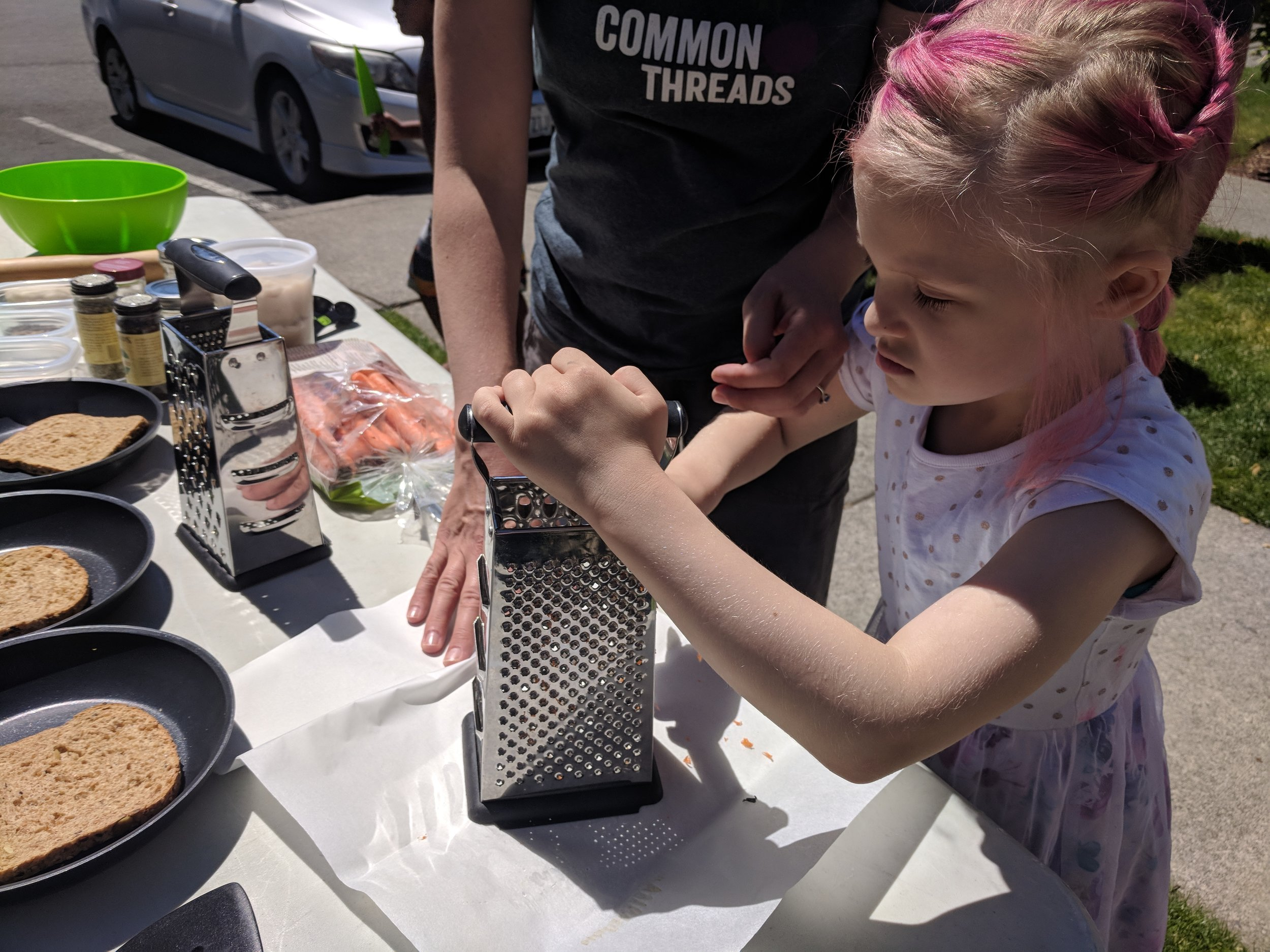 Participant of the Kids Supper Club program through Common Threads Farm, learning to shred carrots
