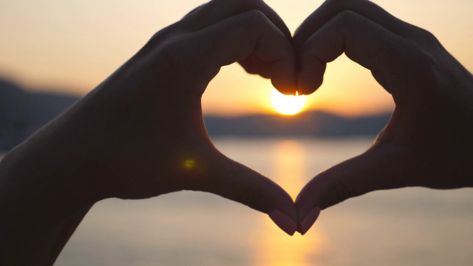 videoblocks-silhouette-of-young-female-hands-making-heart-shape-over-sea-background-with-beautiful-sunset-concept-of-summer-vacation-close-up-slow-motion_rxxtqhyrg_thumbnail-full12.png