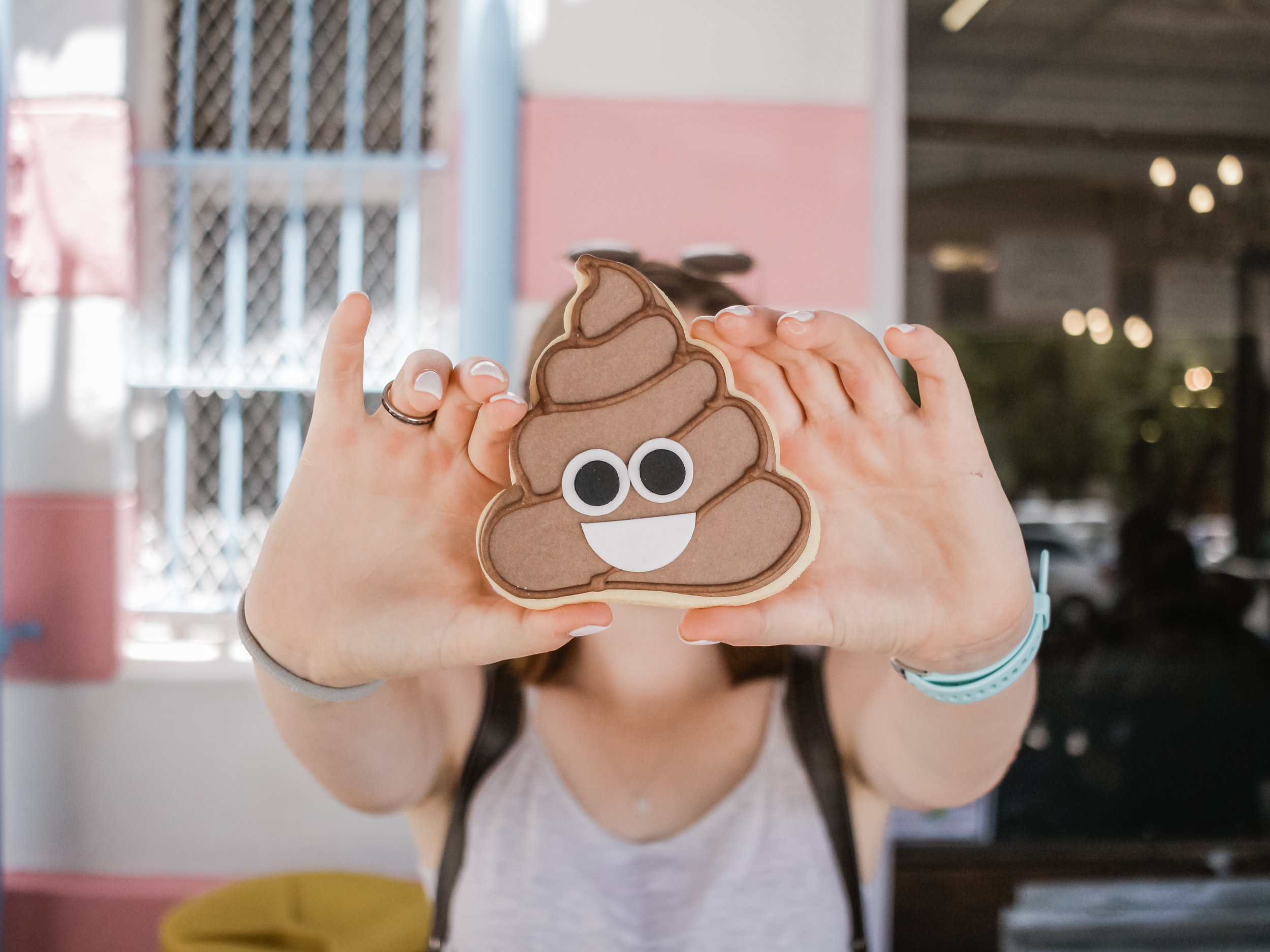 Someone holding a cookie in the shape of the poop emoji