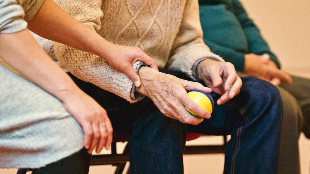 A younger person touching an older person who is holding a stress ball
