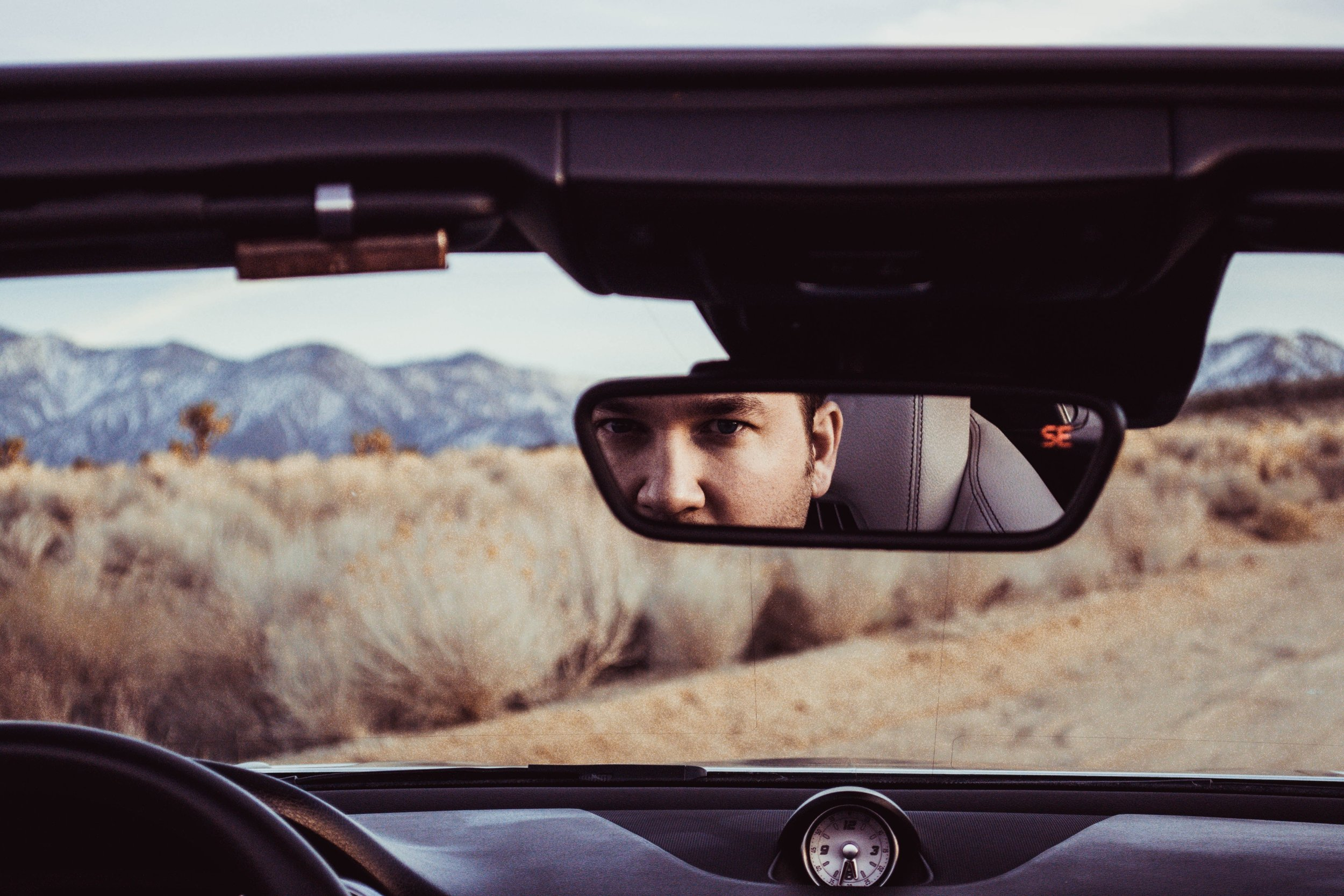 A person reflected in the rear view mirror