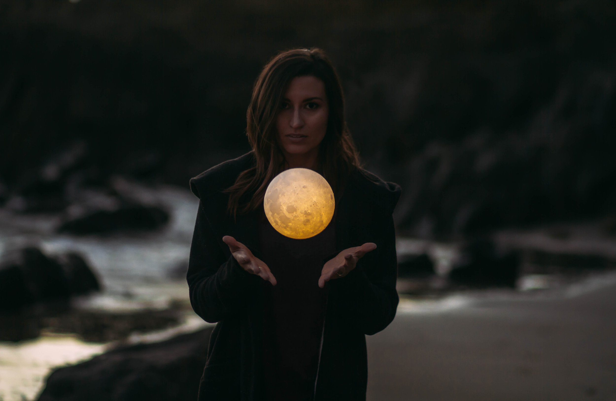 A person seemingly holding the moon above their hands