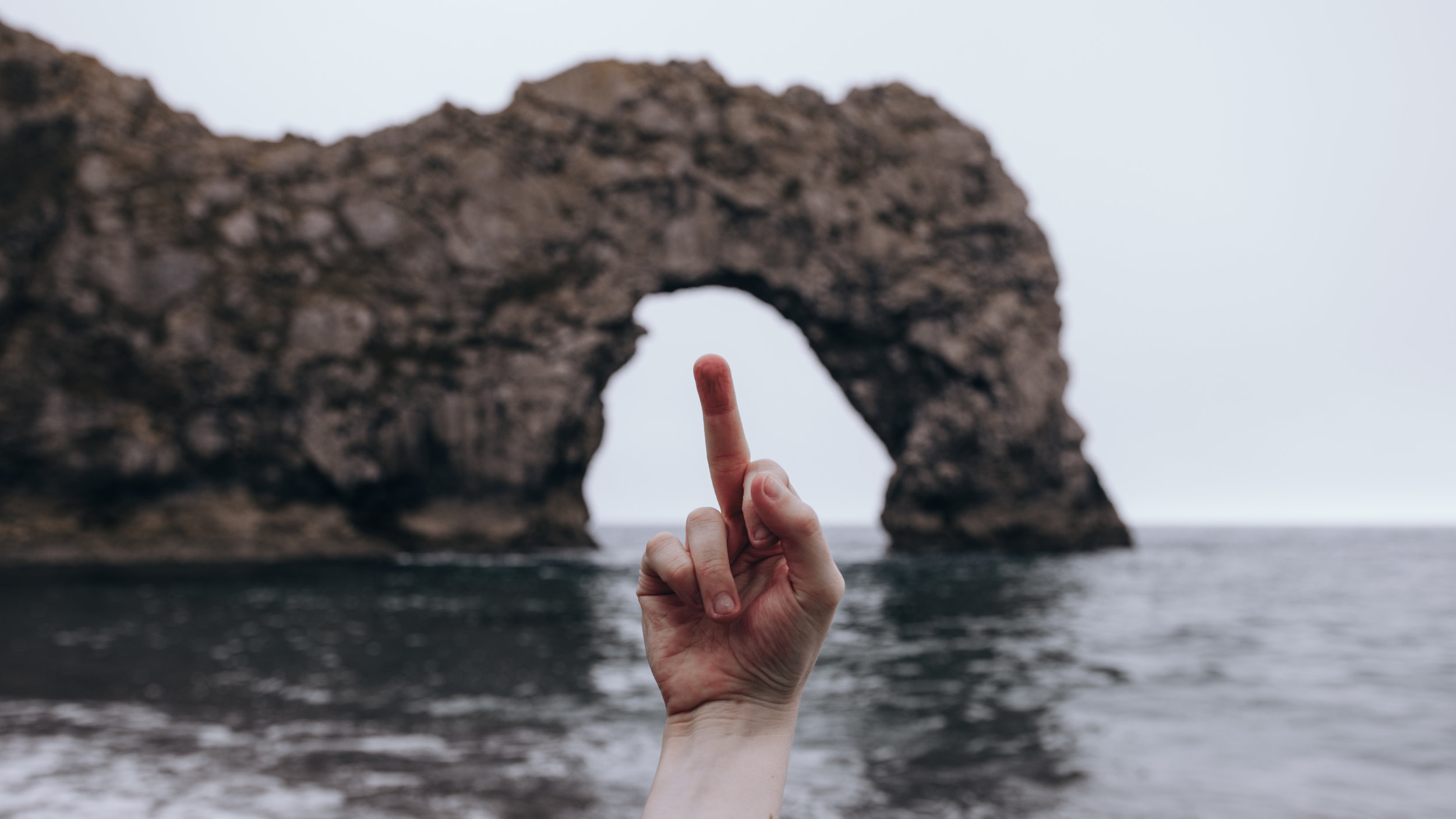 A middle finger held aloft in front of Durdle Door, Dorset, UK