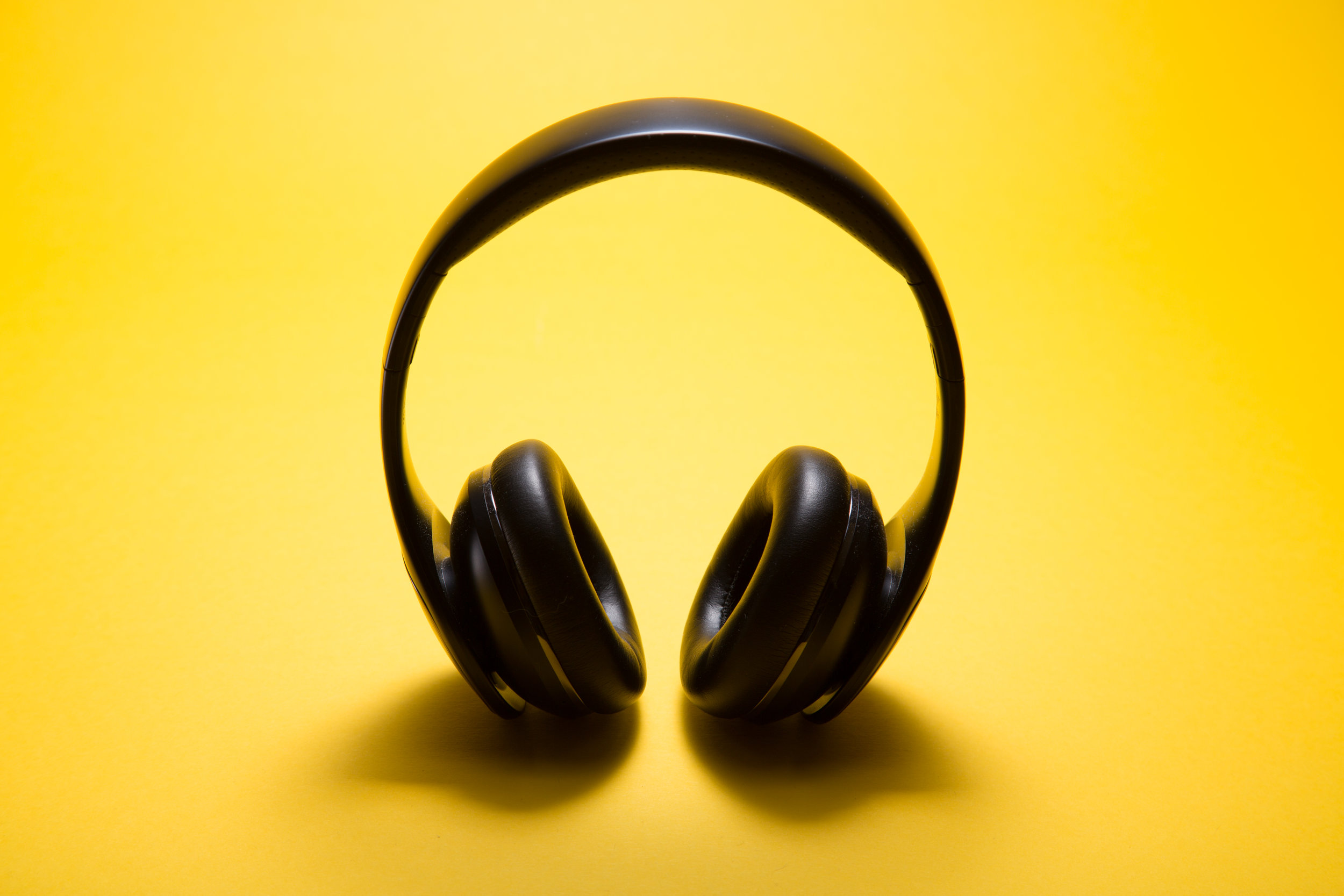 Pair of over-ear headphones on a yellow background