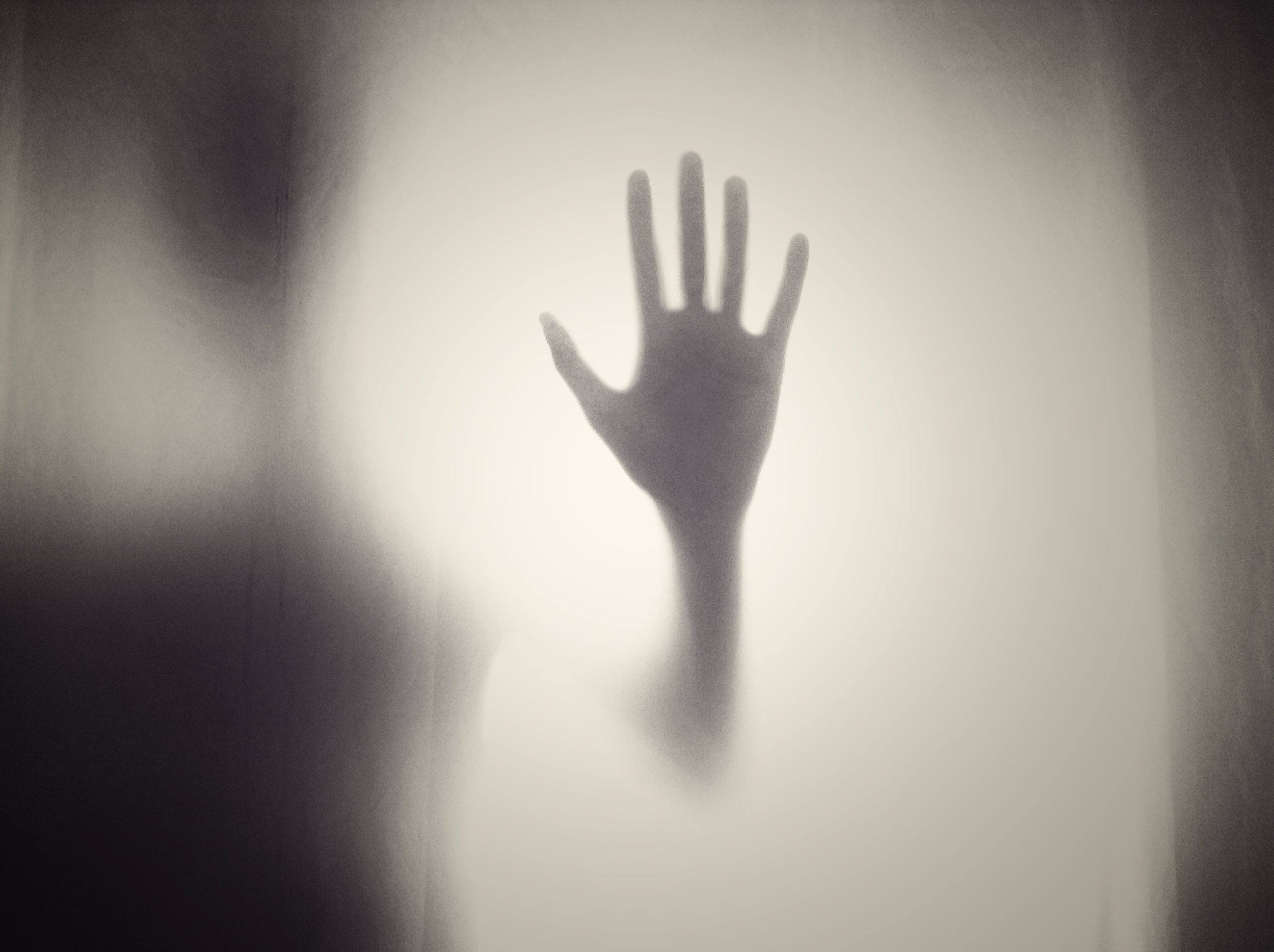 A hand appearing through mist