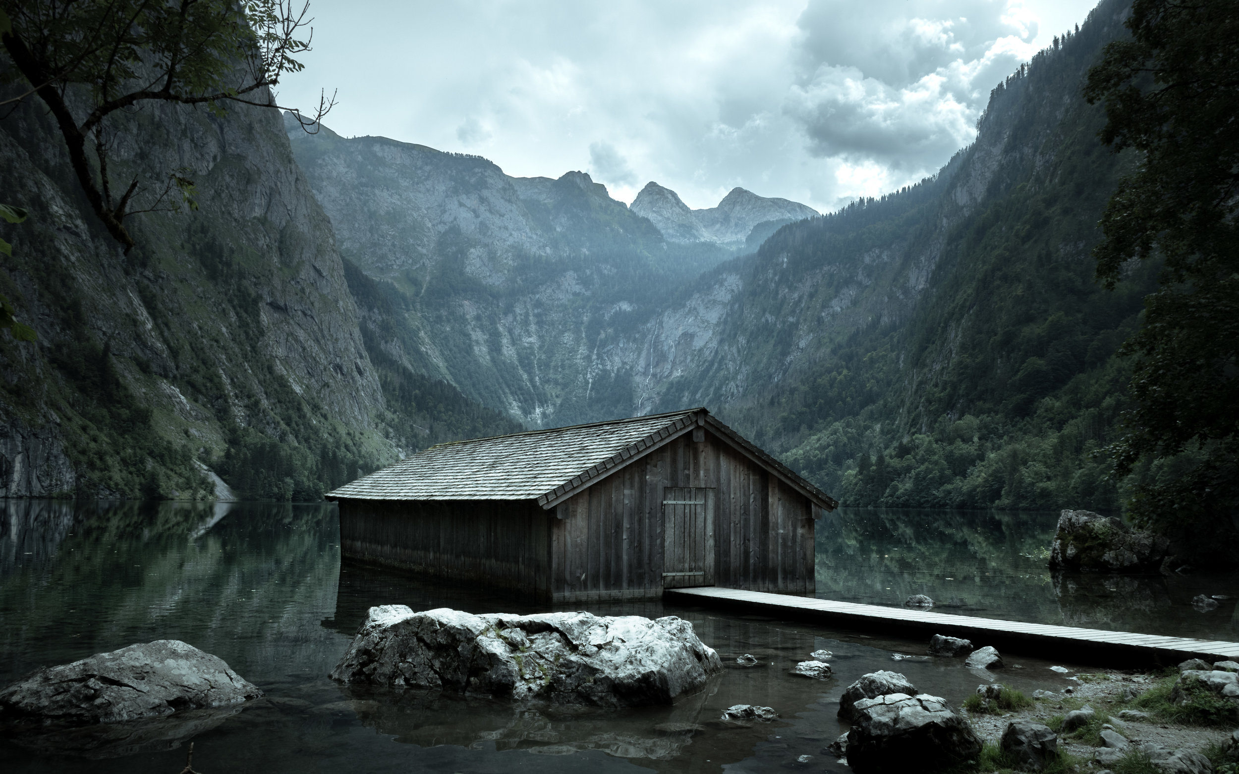 Spooky-looking cabin surrounded by mountains