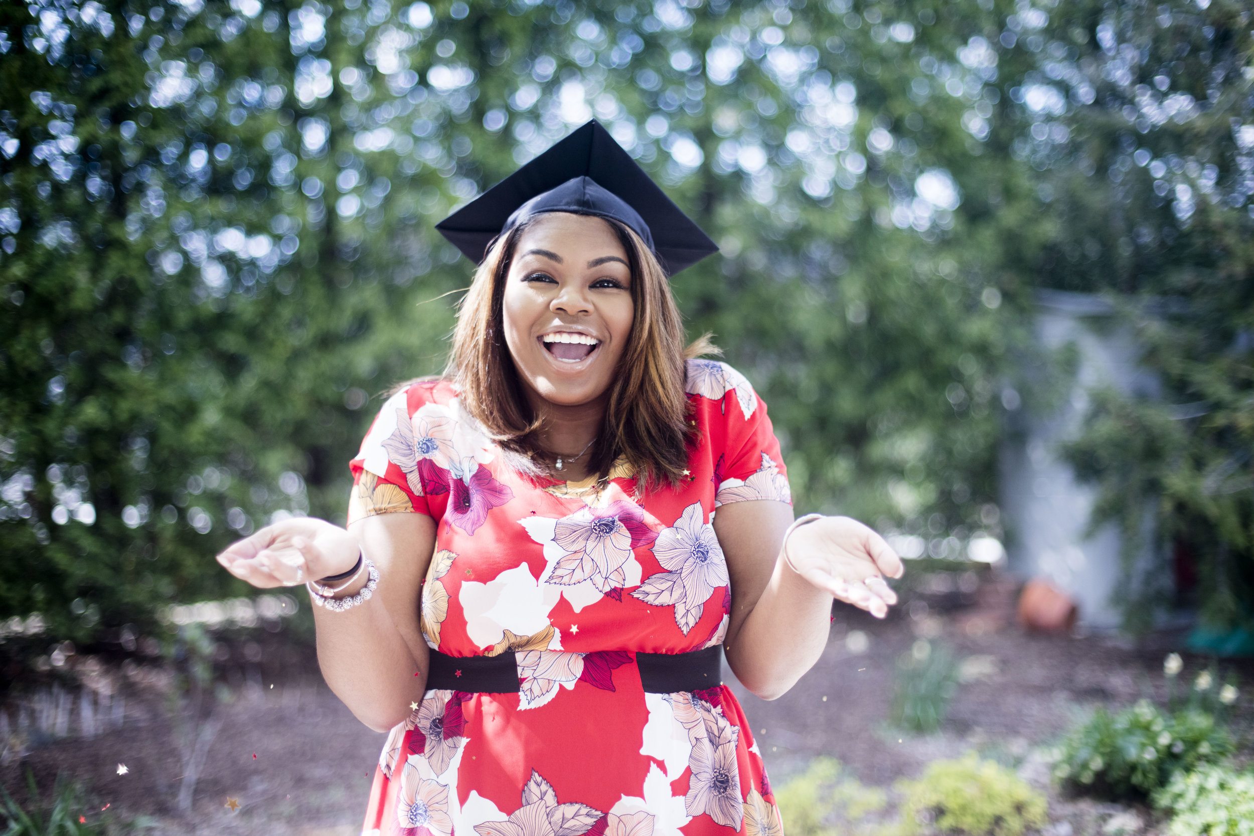 A smiling person in a graduation cap