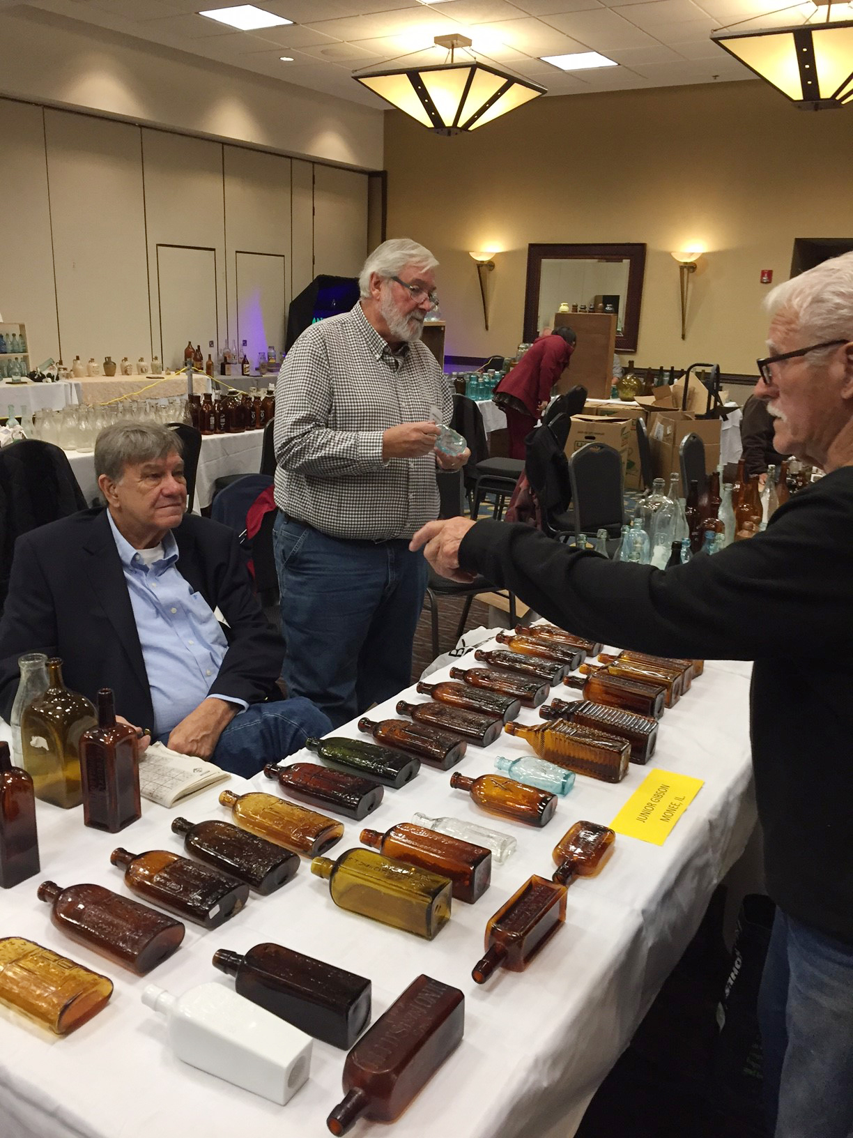 Sales table of Bill Vander Veen (seated) and Jr. Gibson