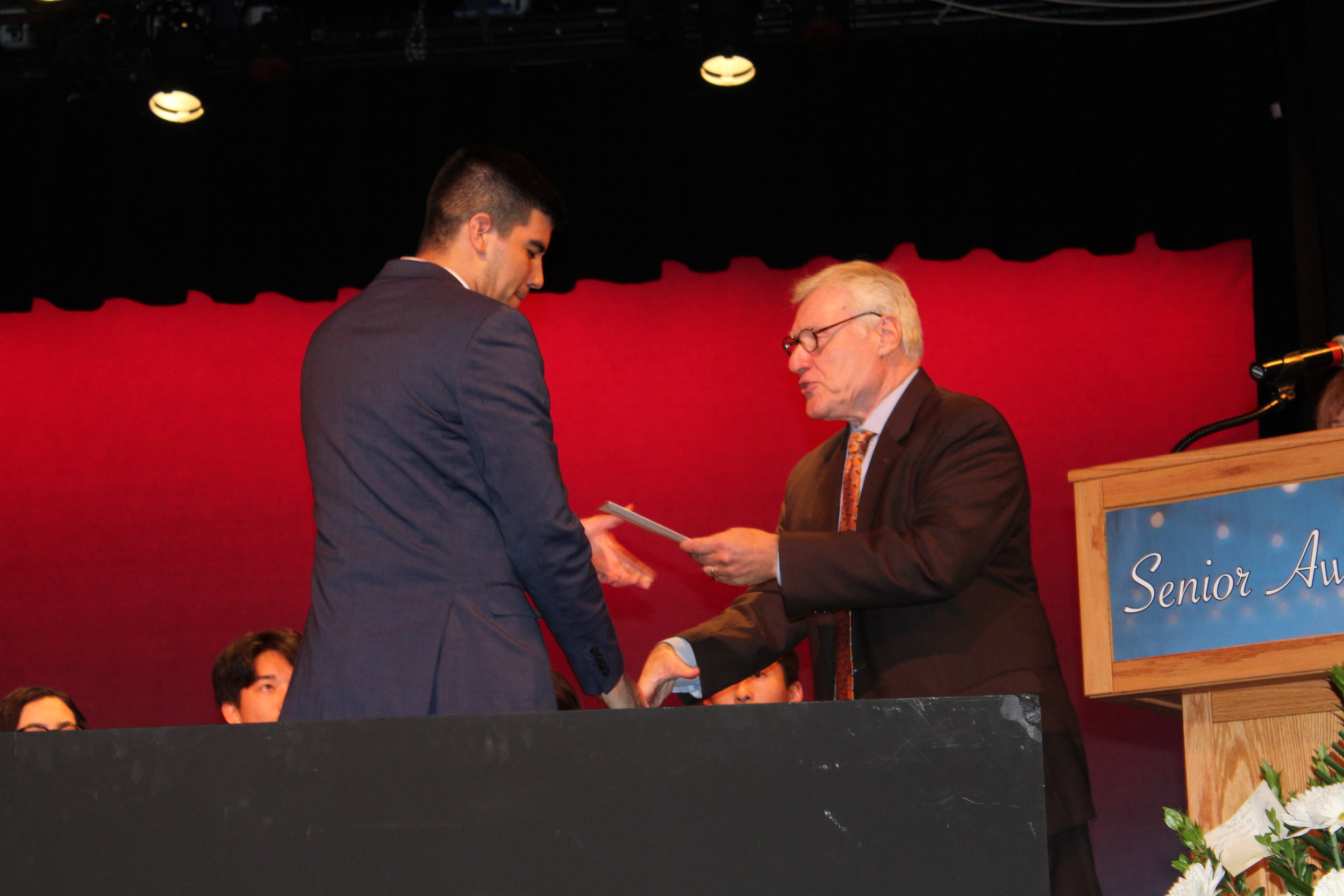 Al Faella hands scholarship to one of the six winners at the 2019 Governor Livingston High School Senior Awards Night.