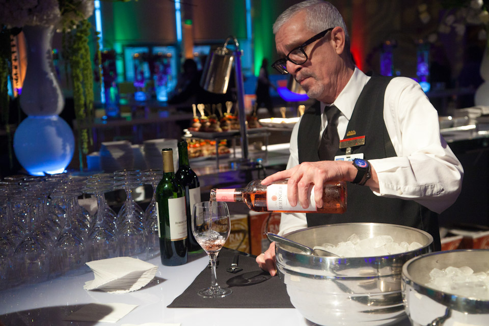 Bartender pouring wine into a glass at an event.