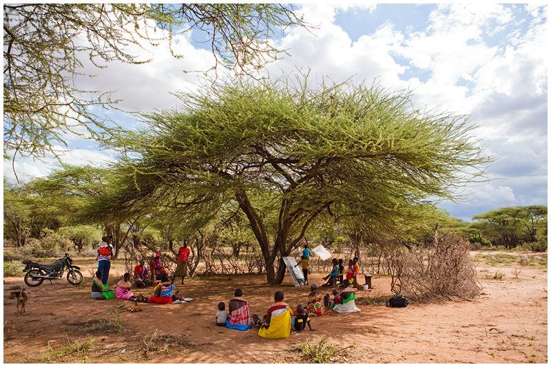 This local community send their children to school under a tree. While the children learn, the mothers sit and watch and chant along, learning their alphabets and counting.