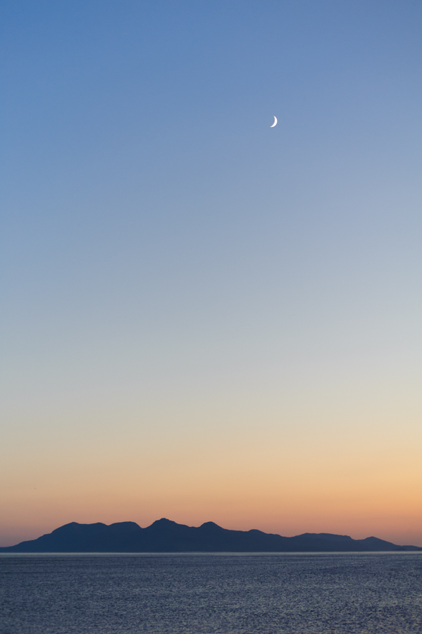 The moon rising above a silhouette of the Cuillin hills on the Isle of Rum in Scotland