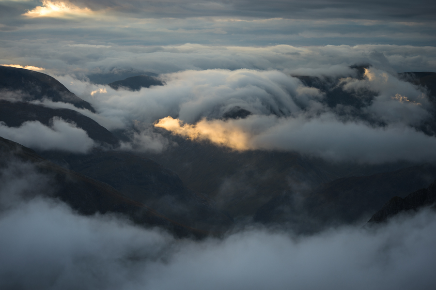 Dawn light piercing clouds in Glen Coe. Captured one Autumn morning after I'd spent the previous evening camped on the summit of Bidean nam Bian, a 1150m high Munro in the West Highlands of Scotland