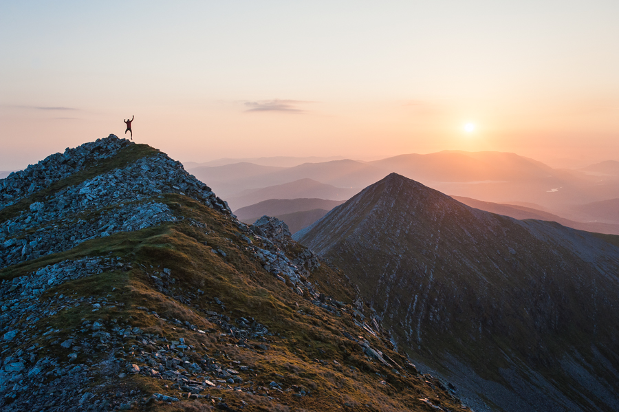 Charlie Lees celebrating the dawn near the summit of Stob Choire Chlaurigh in the Grey Corries in the West Highlands of Scotland