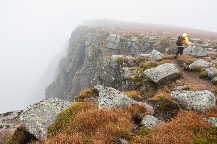 Alex Haken walking along the top of the summit cliffs of Lochnagar, a Munro in the East Highlands of Scotland.