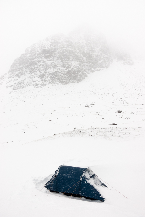 Camping in the snow beneath Sgorr Ruadh, a Munro in the North-West Highlands of Scotland. It took us 4 hours to wade 5km through deep snow to reach this spot, 500m above sea level. At 10:30pm, we were still 1.5km short of the bealach we intended to camp on, my tent pole had snapped whilst I was putting the tent up in strong winds and the pole ripped the fly sheet. Being able to deal with these type of things is one of the reasons I carry a decent amount of gear with me into Scotland's winter hills.