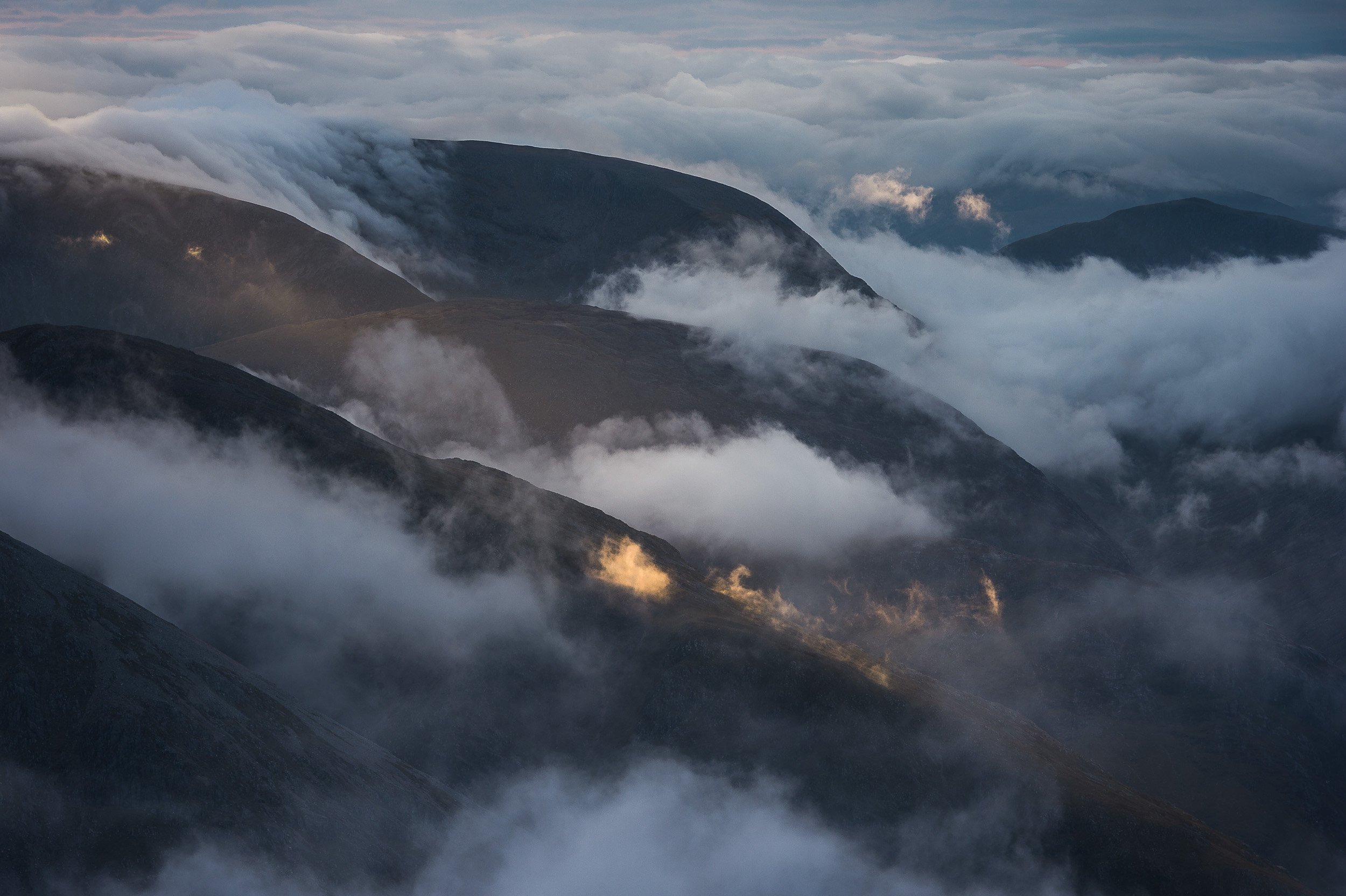 Clouds forming at dawn in the glens to the east of Stob Coire nan Lochan above Glen Coe in the West Highlands of Scotland.