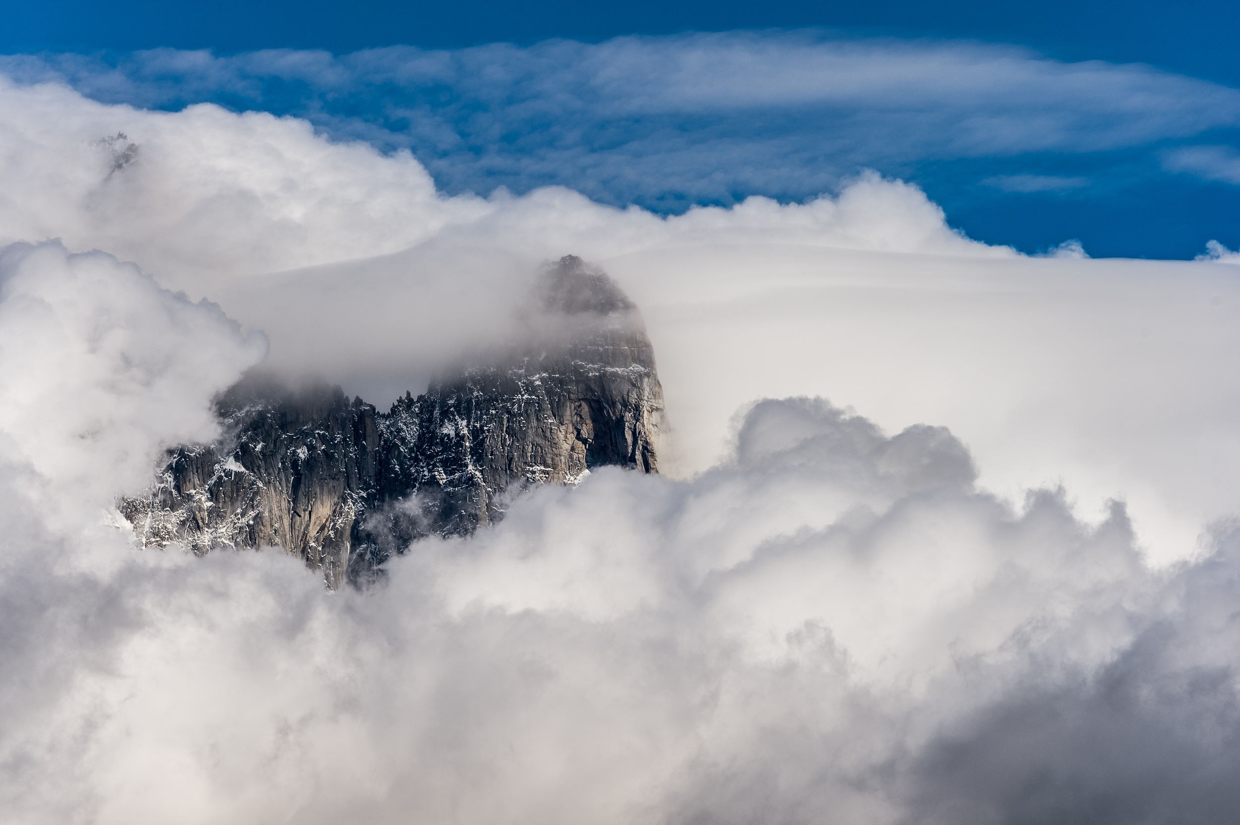 The iconic peak of Aiguille du Dru peeks out of the clouds in the Chamonix region of France.
