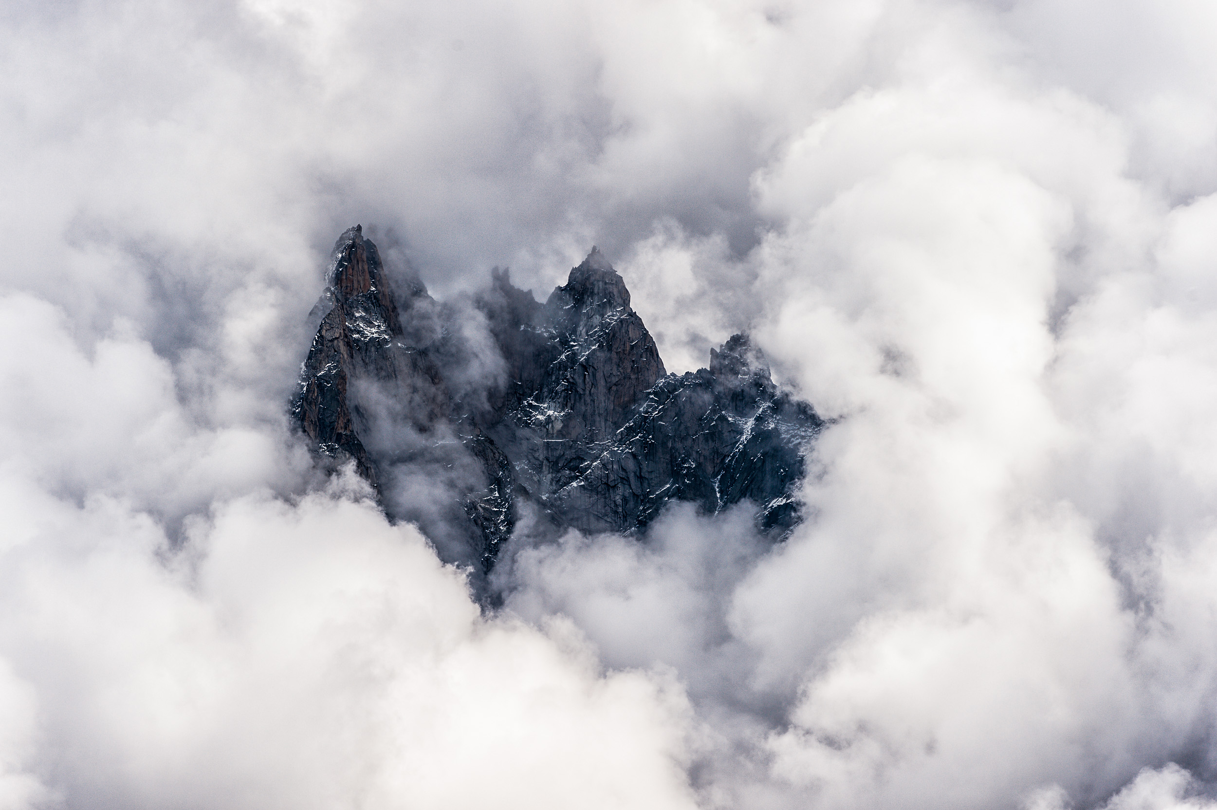 Afternoon clouds surround the Aiguille de Blaitière, Aiguille des Ciseaux, Aiguille du Fou in the Mont Blanc region of France.