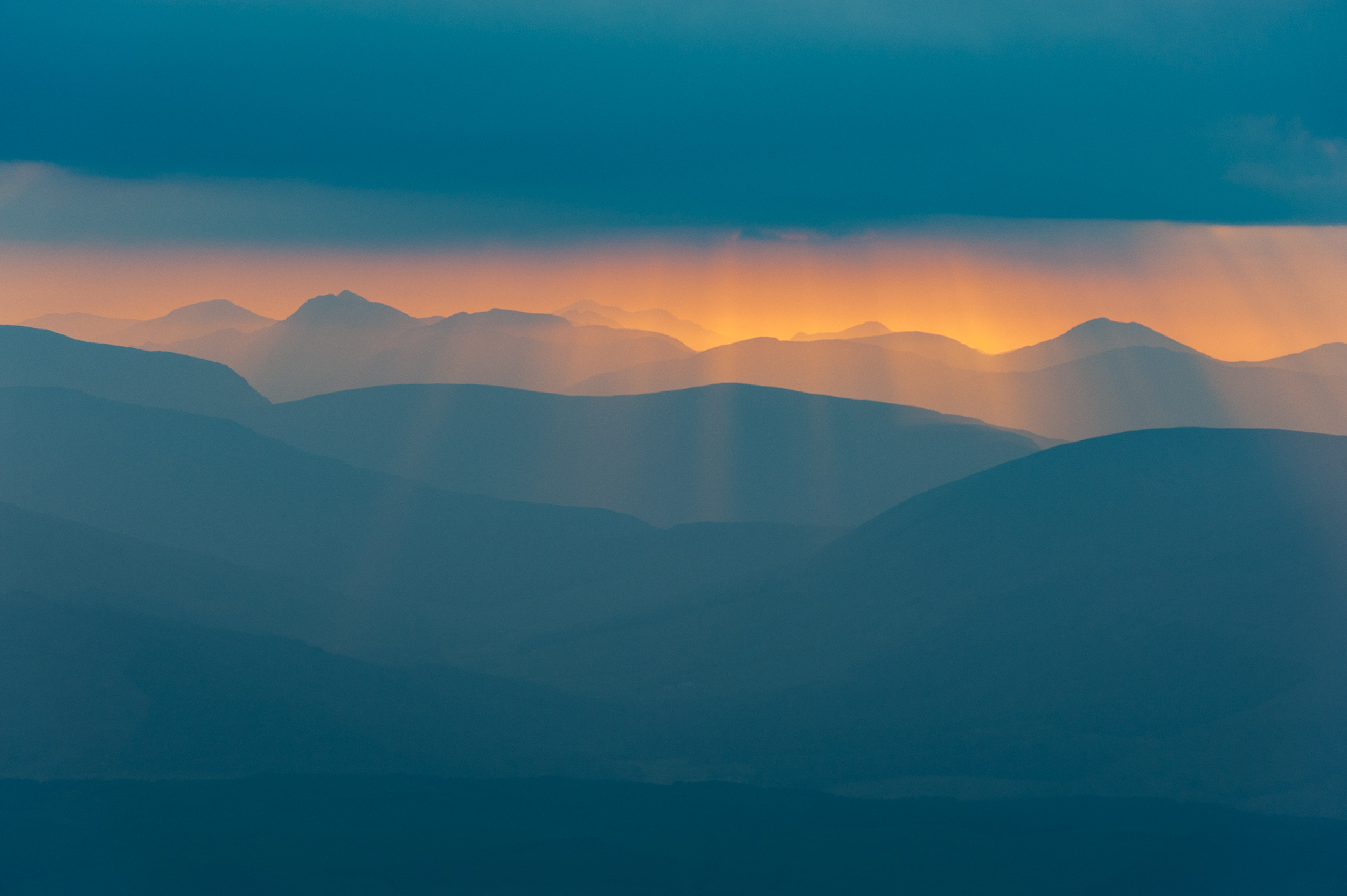 Sunset lights up Meall na Teanga and other peaks in the Glengarry Forest from a bivvy on Stob Choire Claurigh in the Grey Corries, West Highlands of Scotland.