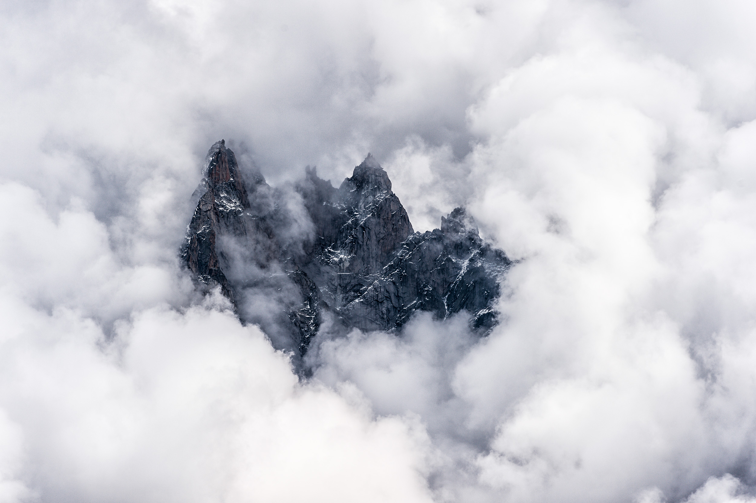 Afternoon clouds surrounding the summits of Aiguille de Blaitière, Aiguille des Ciseaux, Aiguille du Fou in the Mont Blanc region of France.