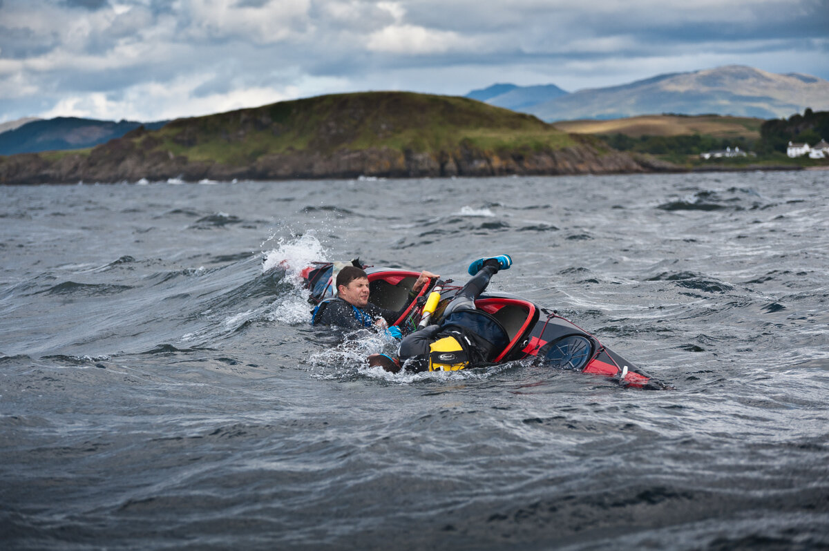 Competitors capsize in rough waters during the Oban Sea Kayaking Race, an annual 20km race around the island of Kerrera off the west coast of Scotland. The pair were back in their boat fairly quickly, obviously confident that their skills and experience (at what I'd call 'self-arrest' in mountaineering terms) were sufficient for them to be confident they could manage any risks they'd experience during the race, e.g. falling overboard.