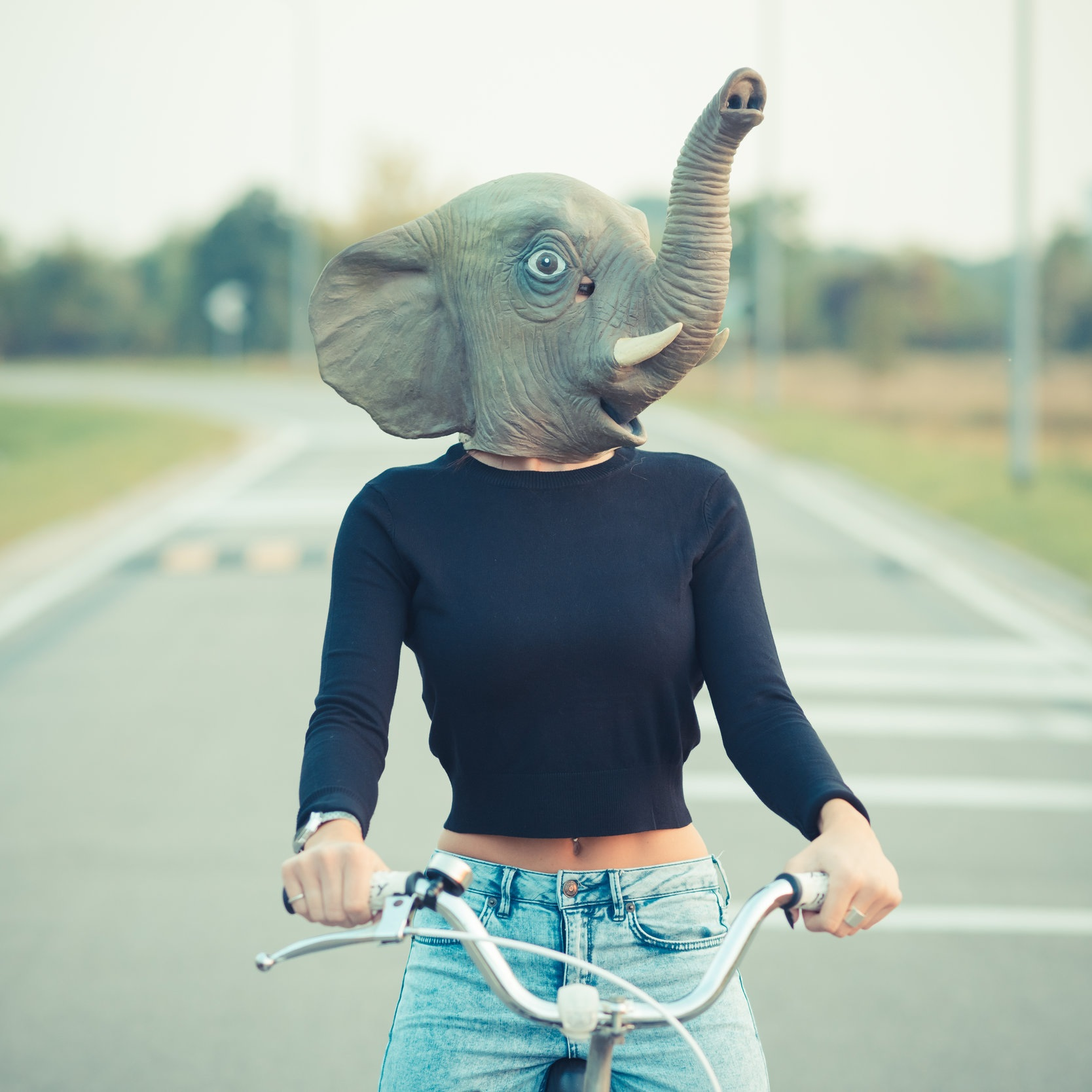 graphicstock-elephant-mask-young-beautiful-brunette-straight-hair-woman-using-bike-outdoor_SaK1U7jkb.jpg