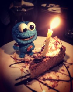 Cookie Monster figurine stands next to birthday cake