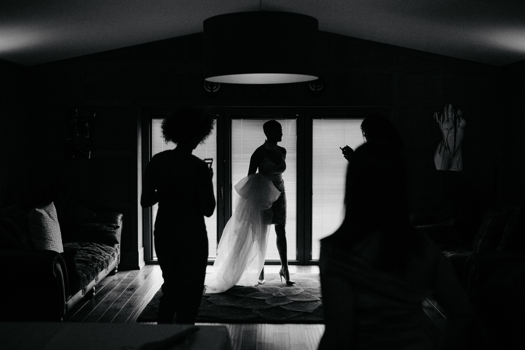 A bride stands in front of a window in her dress before her yorkshire wedding