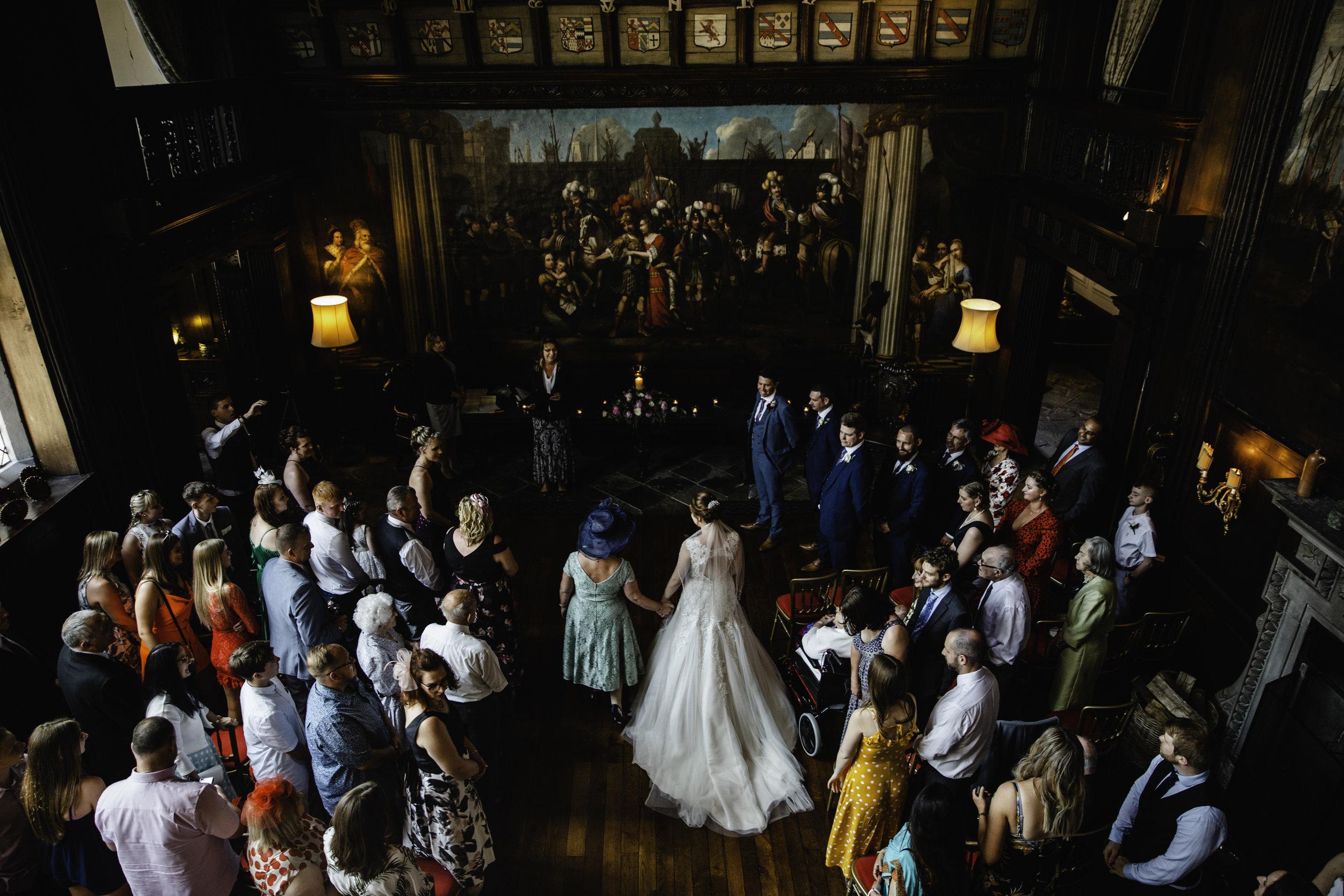 Wide angle lens photograph of bride walking down aisle at Adlington Hall
