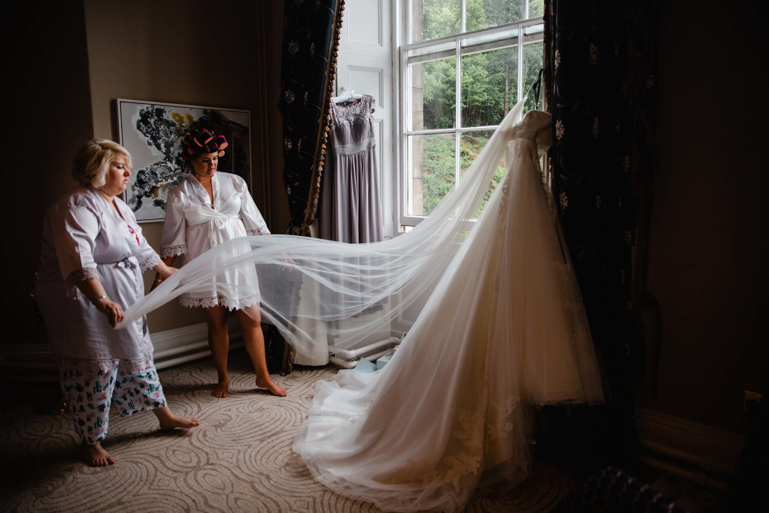 bridesmaid holding wedding dress veil in bridal suite at haigh hall
