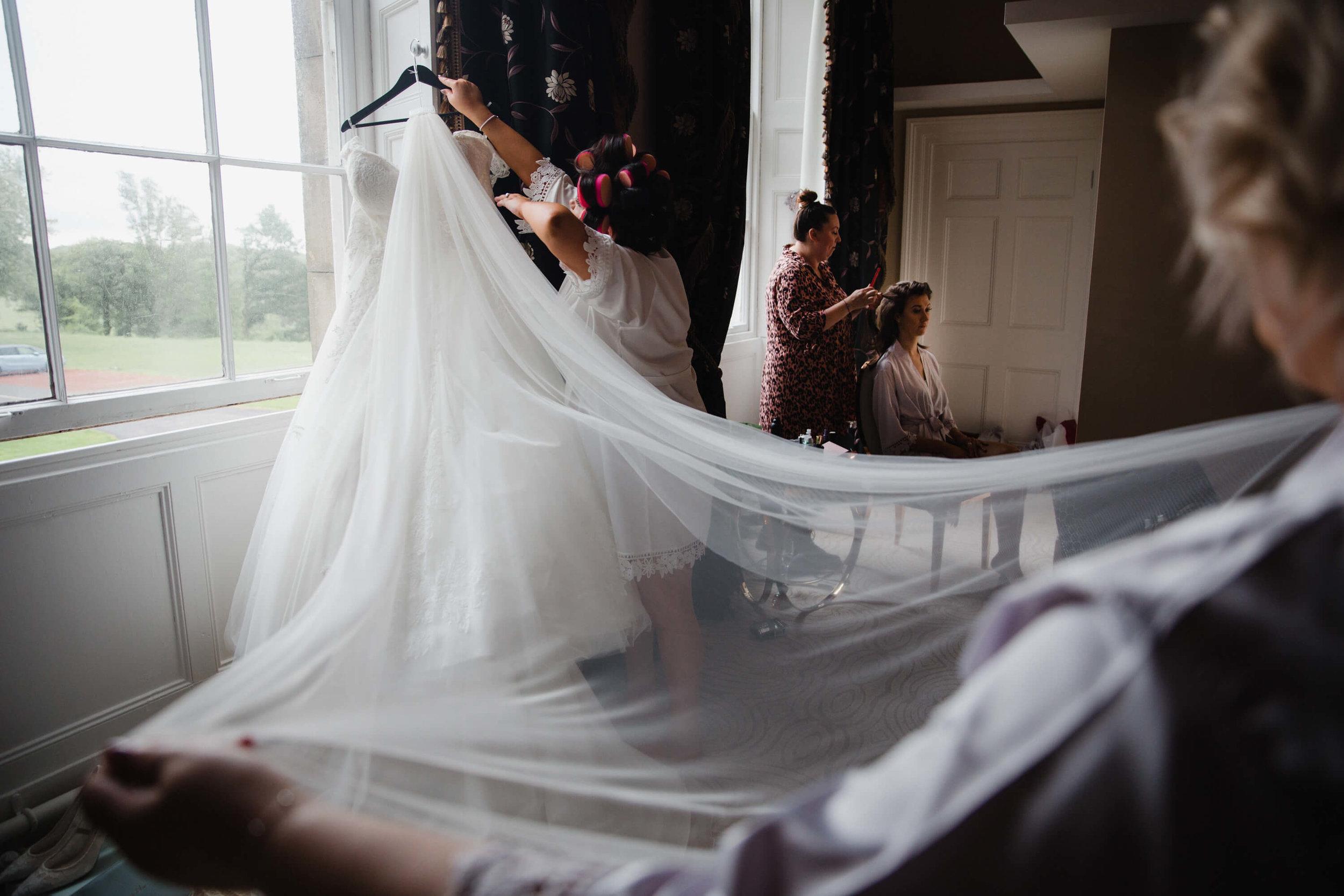 bridesmaid holding wedding dress veil for bride during wedding preparation