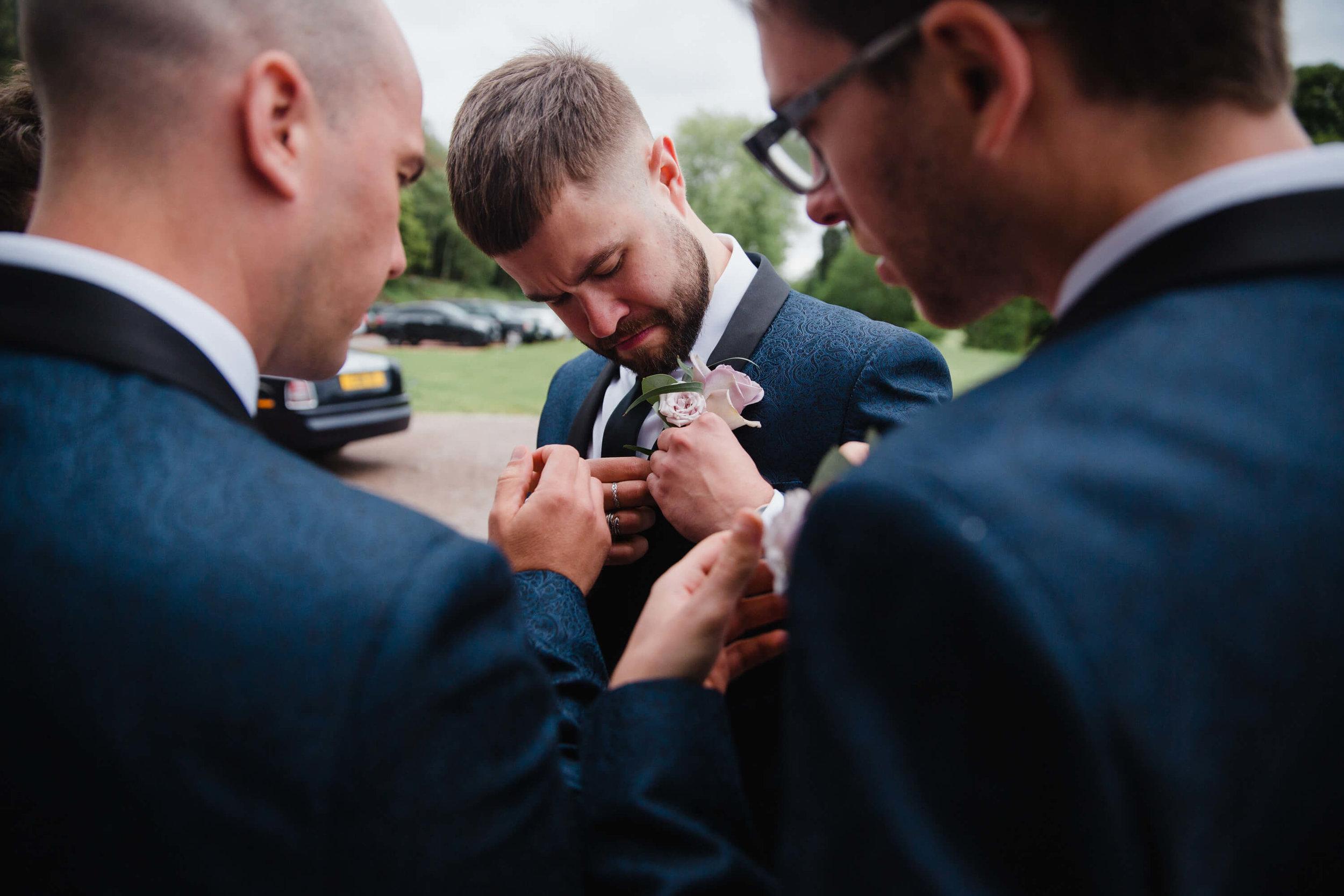 usher fixing button hole flower to jacket lapel