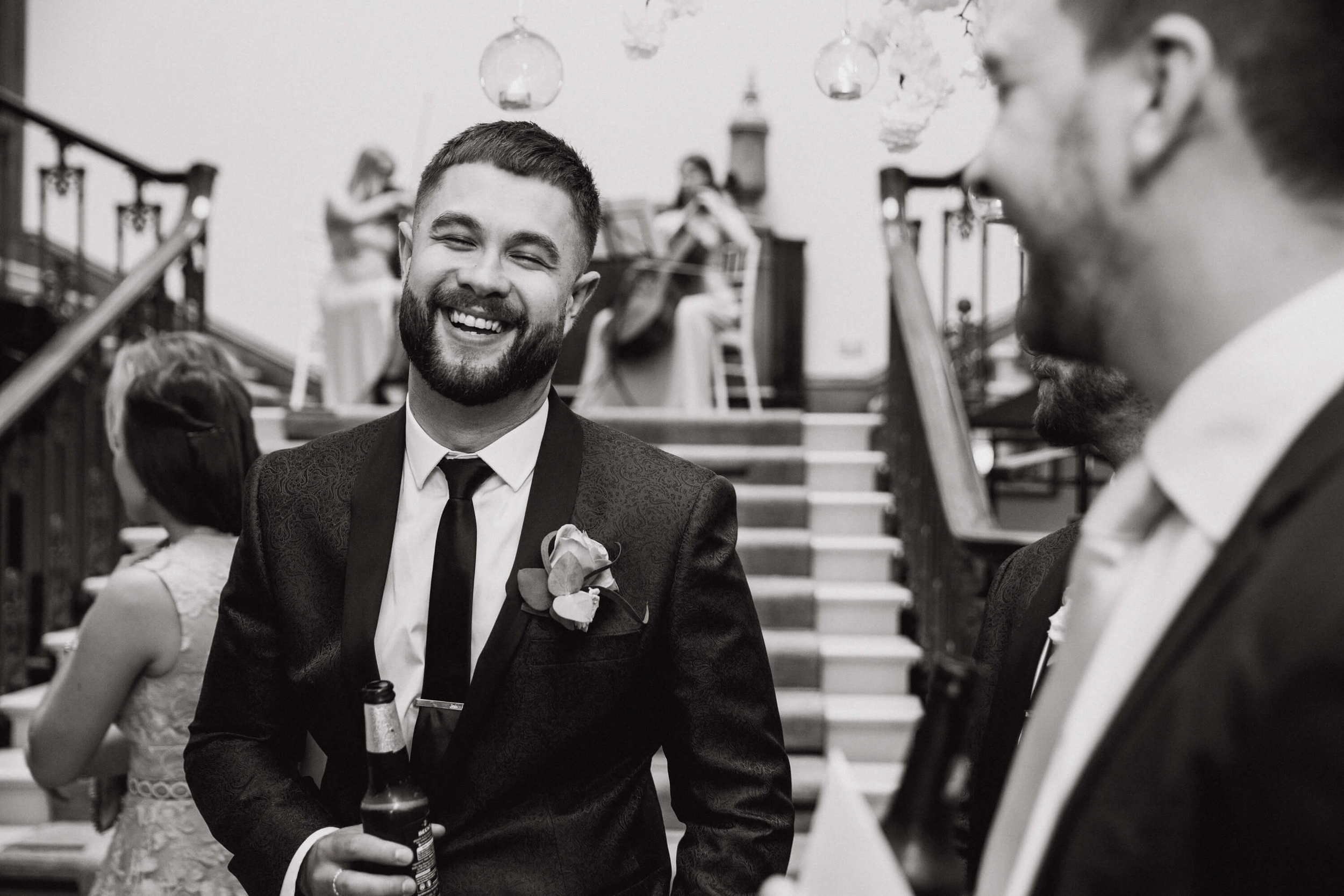 black and white photograph of groomsman laughing