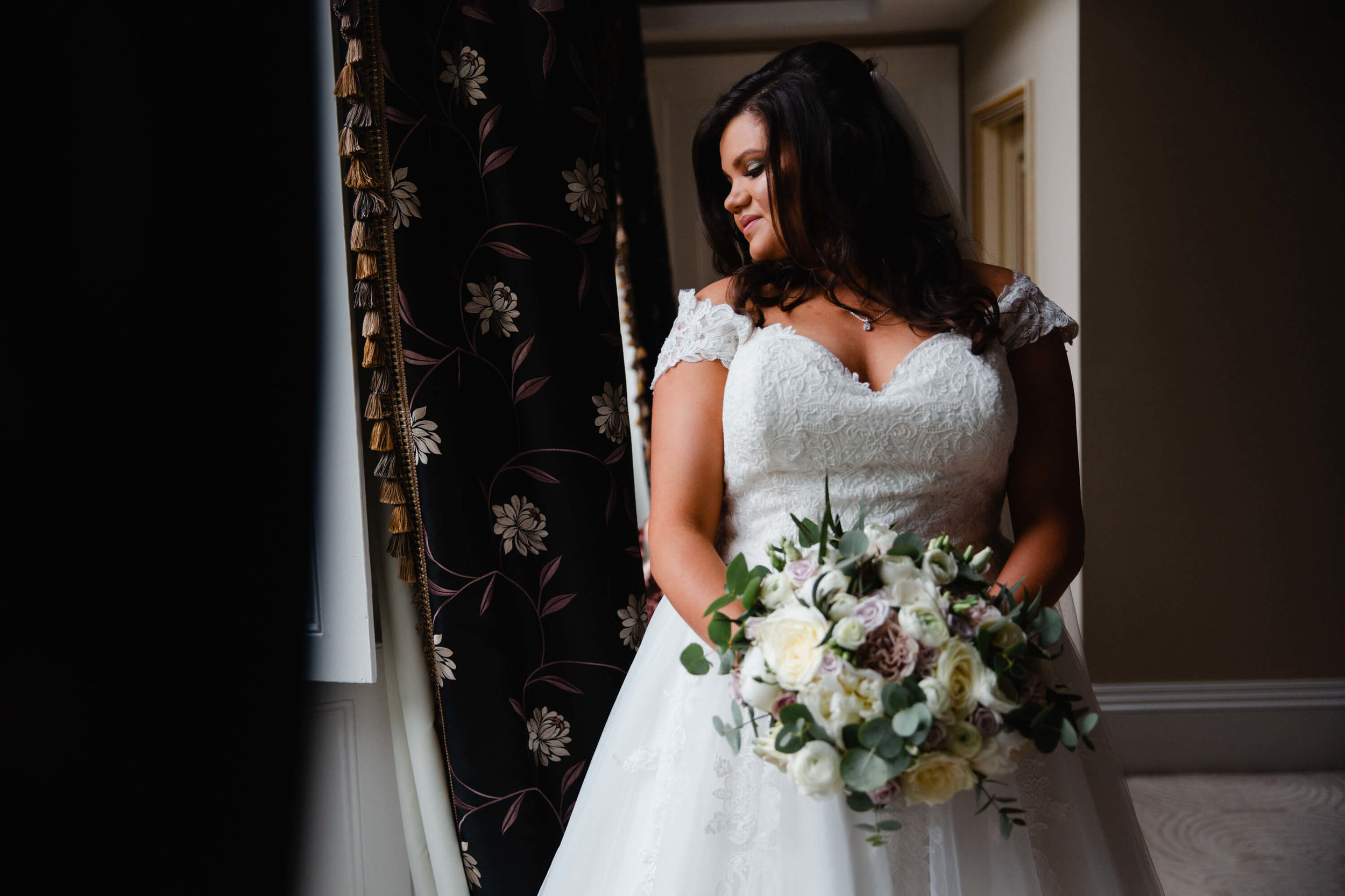 portrait of bride in window holding bouquet of flowers at haigh hall