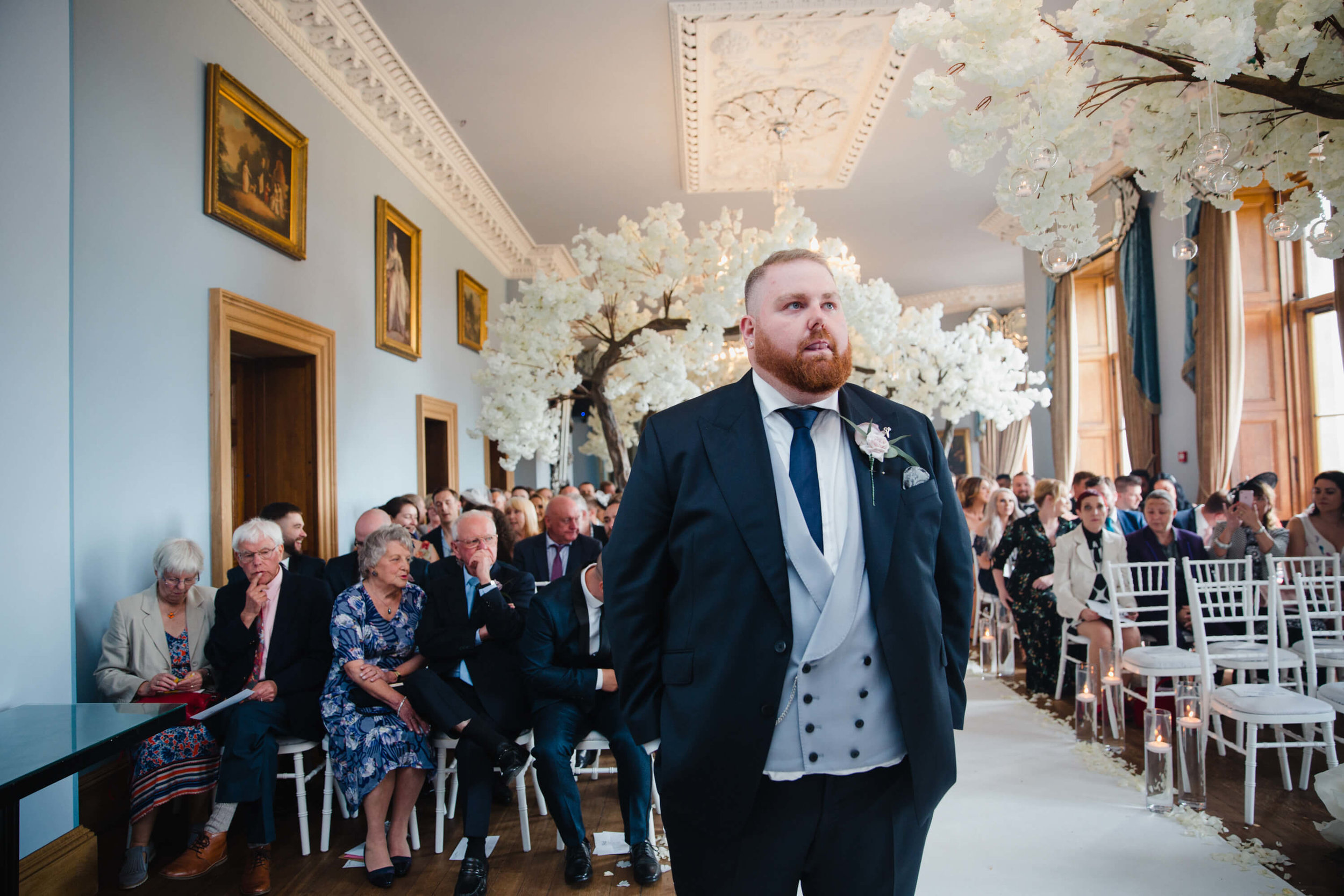 groom stood on top of aisle waiting for bride during haigh hall ceremony