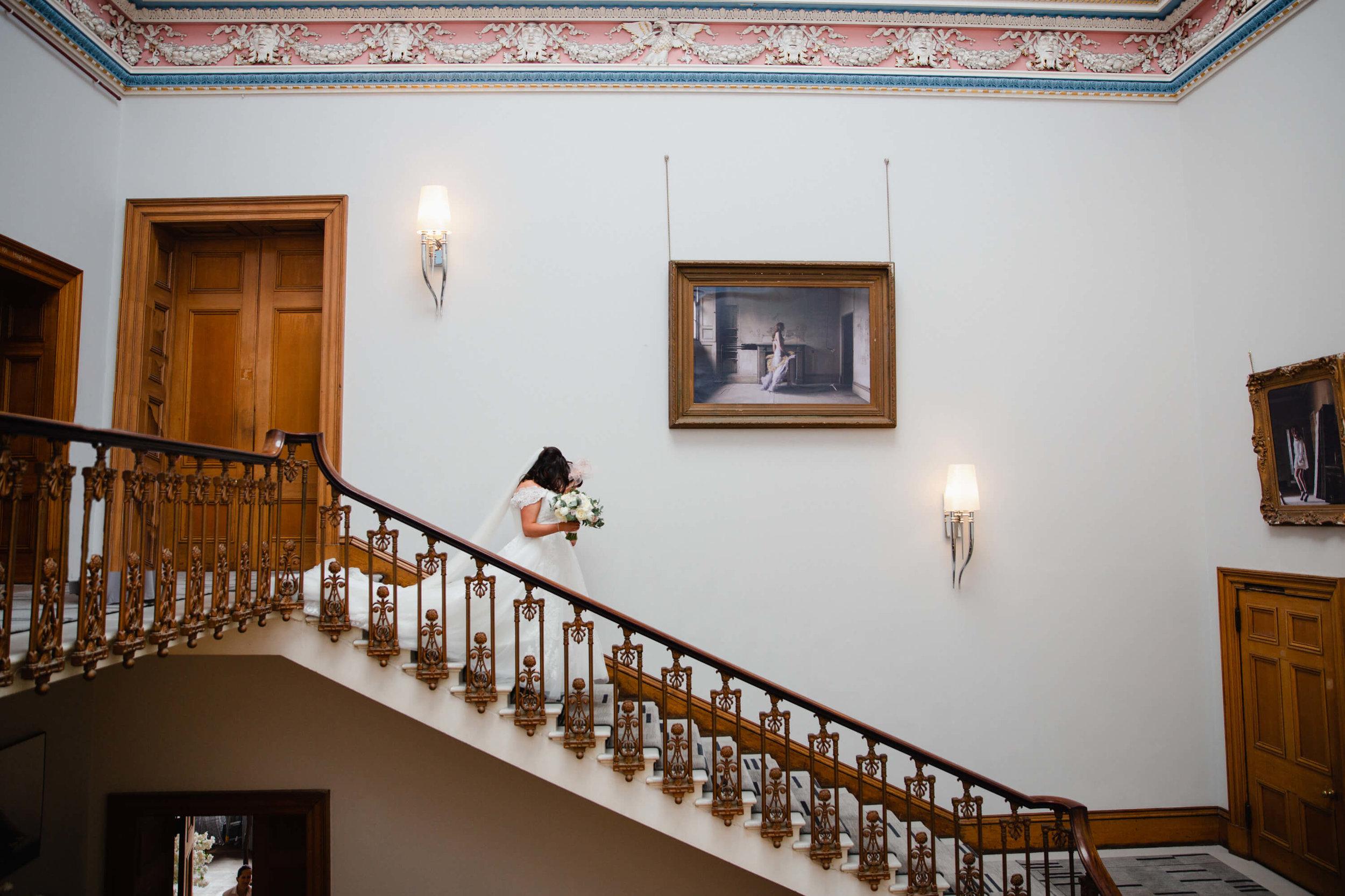 bride walking down staircase at haigh hall
