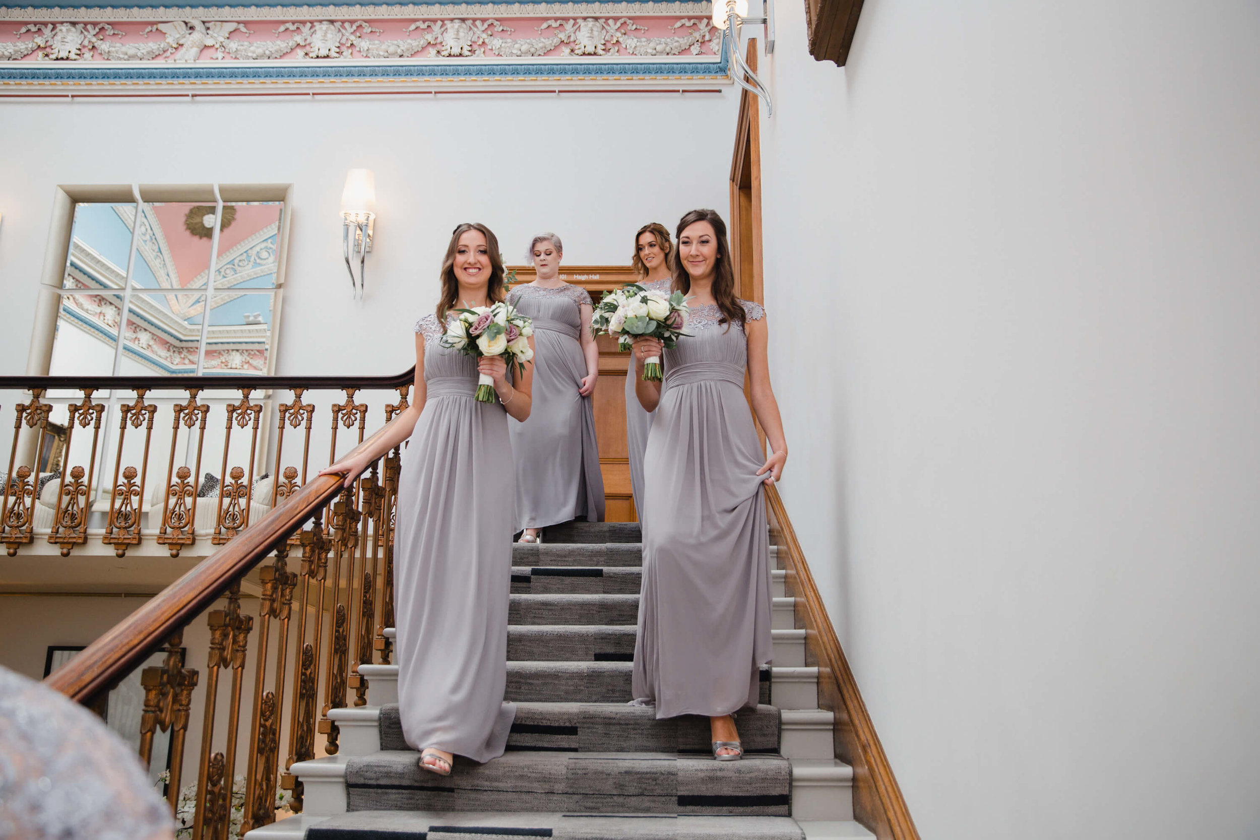 bridesmaids holding bouquets walking down staircase on way to ceremony