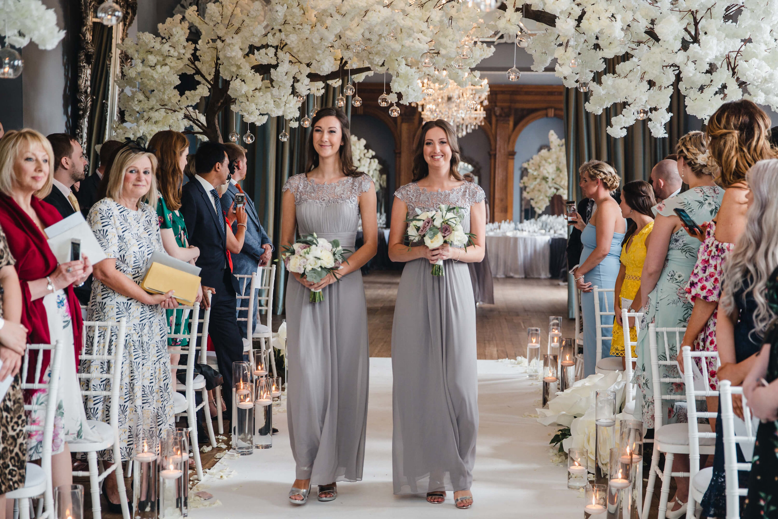 bridesmaids walking down ceremony aisle under blossom trees