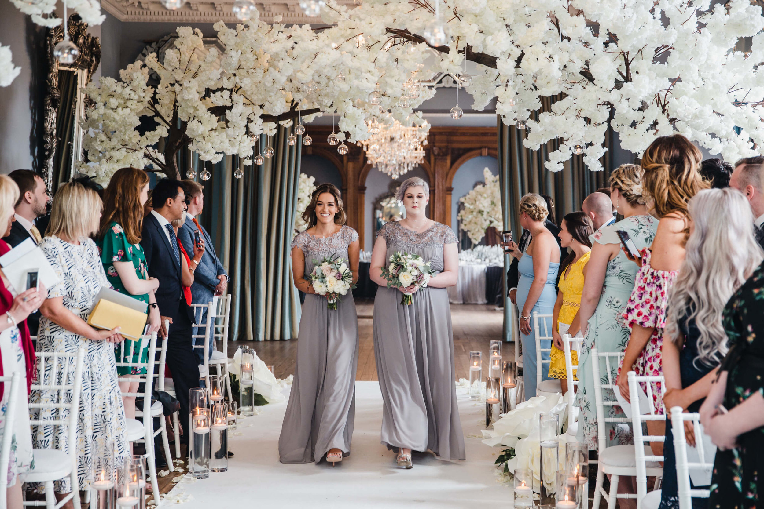 maid of honour walking down wedding aisle at beginning of ceremony