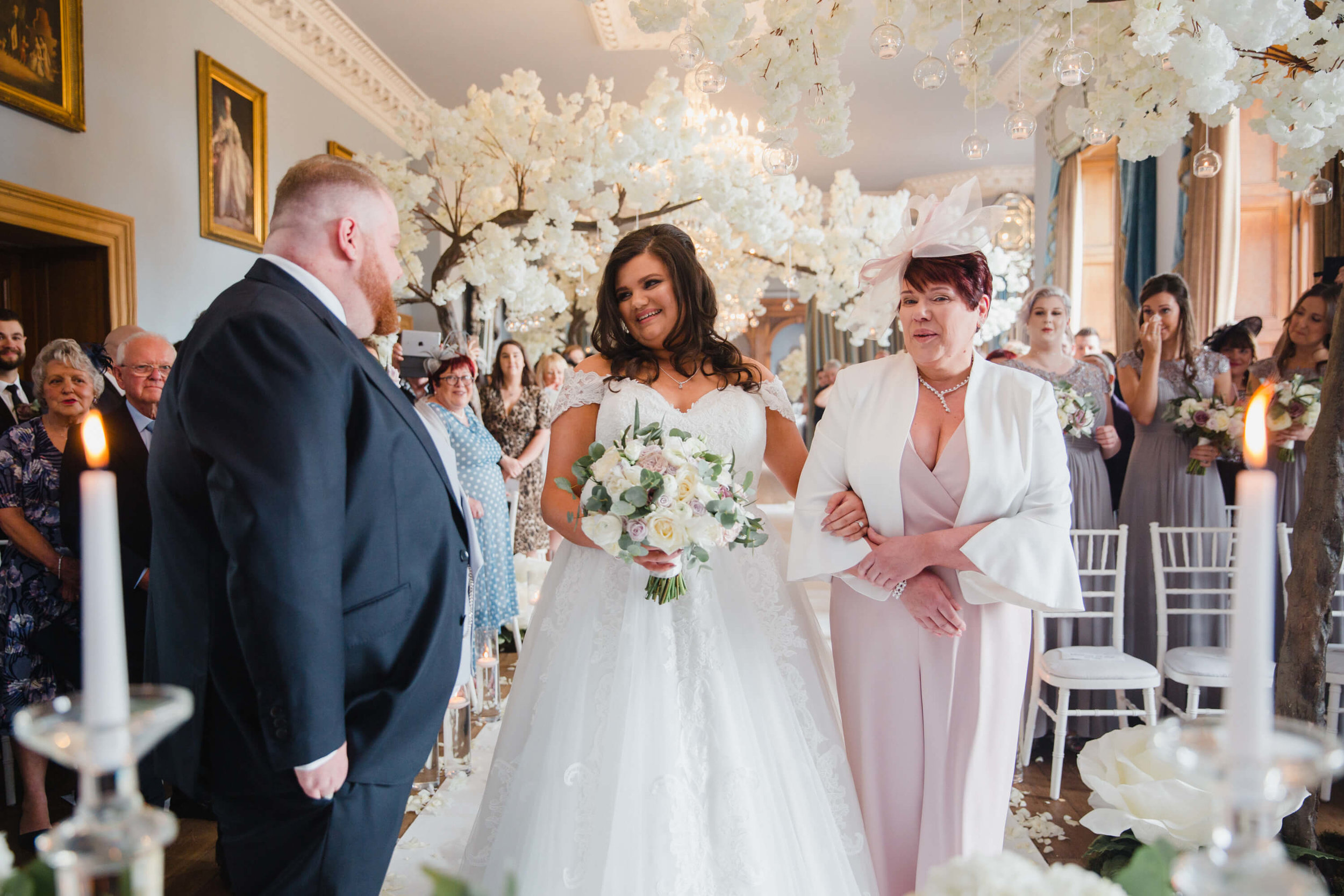 groom greeting bride at top of aisle for wedding ceremony at haigh hall